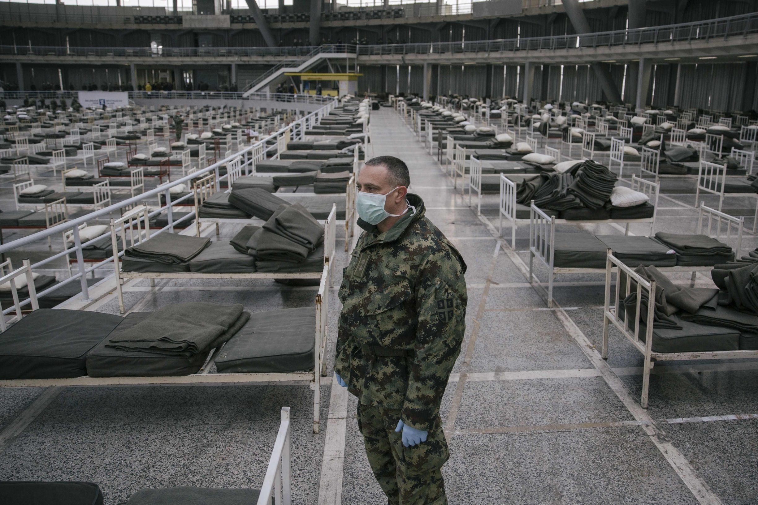 TOPSHOT - A Serbian military personnel wearing a protective mask stands amongst beds set up inside a hall of the Belgrade Fair to accommodate people who suffer mild symptoms of coronavirus disease (COVID-19) on March 24, 2020. - More than 200,000 coronavirus cases have been declared in Europe, according to an AFP tally on March 24, 2020. (Photo by Vladimir Zivojinovic / AFP)