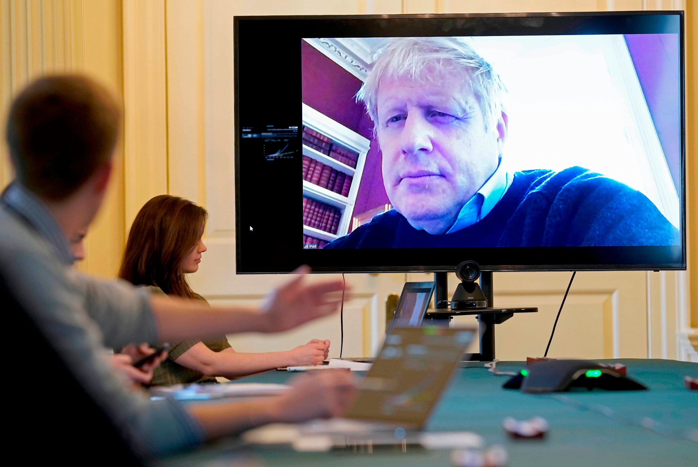 A handout picture released by 10 Downing Street, the office of the British prime minister on March 28, 2020, shows an image of Britain's Prime Minister Boris Johnson on a screen as he remotely chairs the morning novel coronavirus Covid-19 meeting by video link, in Downing Street in central London. - The two men leading Britain's fight against the coronavirus -- Prime Minister Boris Johnson and his Health Secretary Matt Hancock -- both announced Friday they had tested positive for COVID-19, as infection rates accelerated and daily death rate rose sharply. (Photo by - / 10 Downing Street / AFP) / RESTRICTED TO EDITORIAL USE - MANDATORY CREDIT