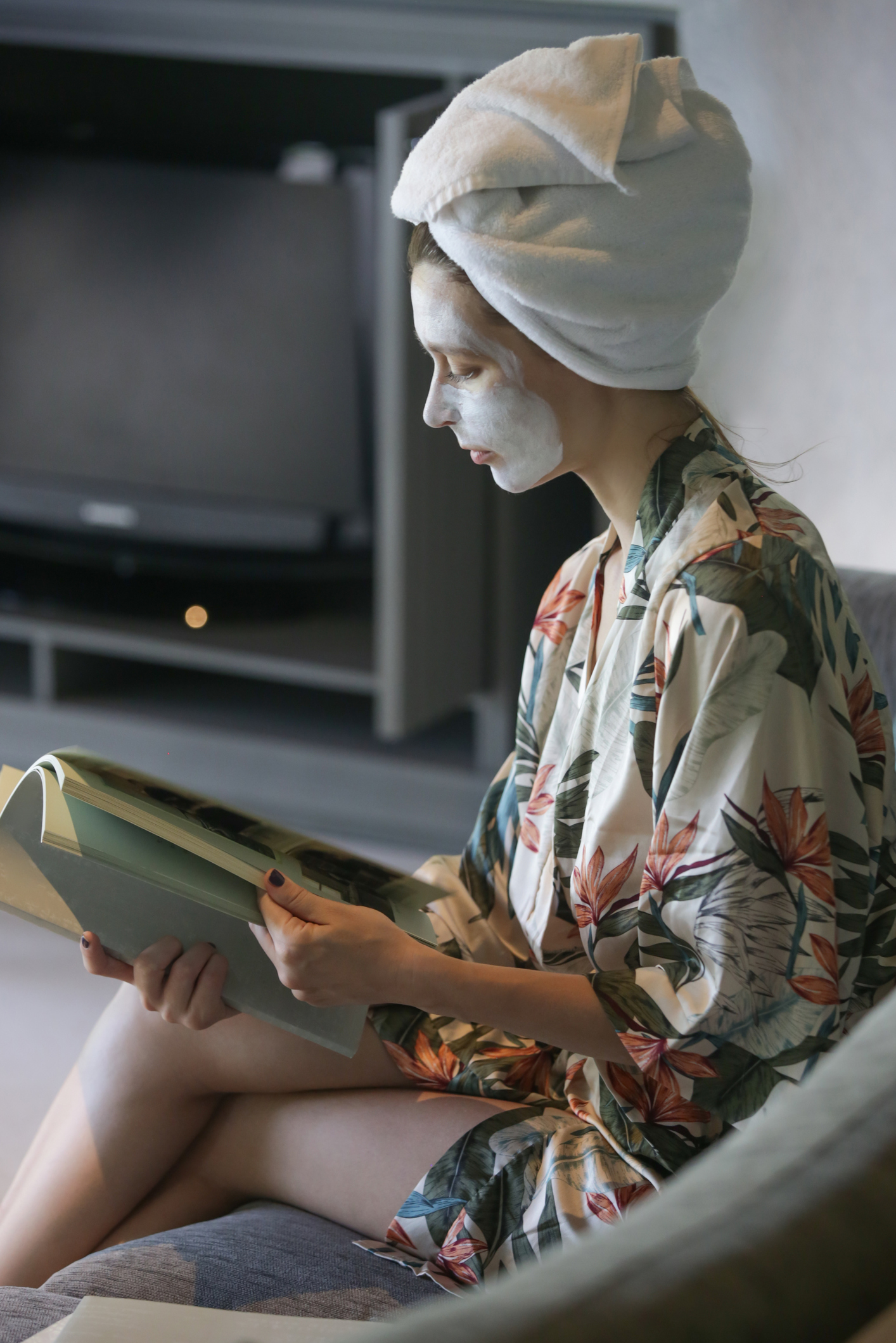Young woman sitting at home with face beauty mask while reading a book. Cozy time at home. Self time and home spa concept. Coronavirus outbreak and self-quarantining concept.