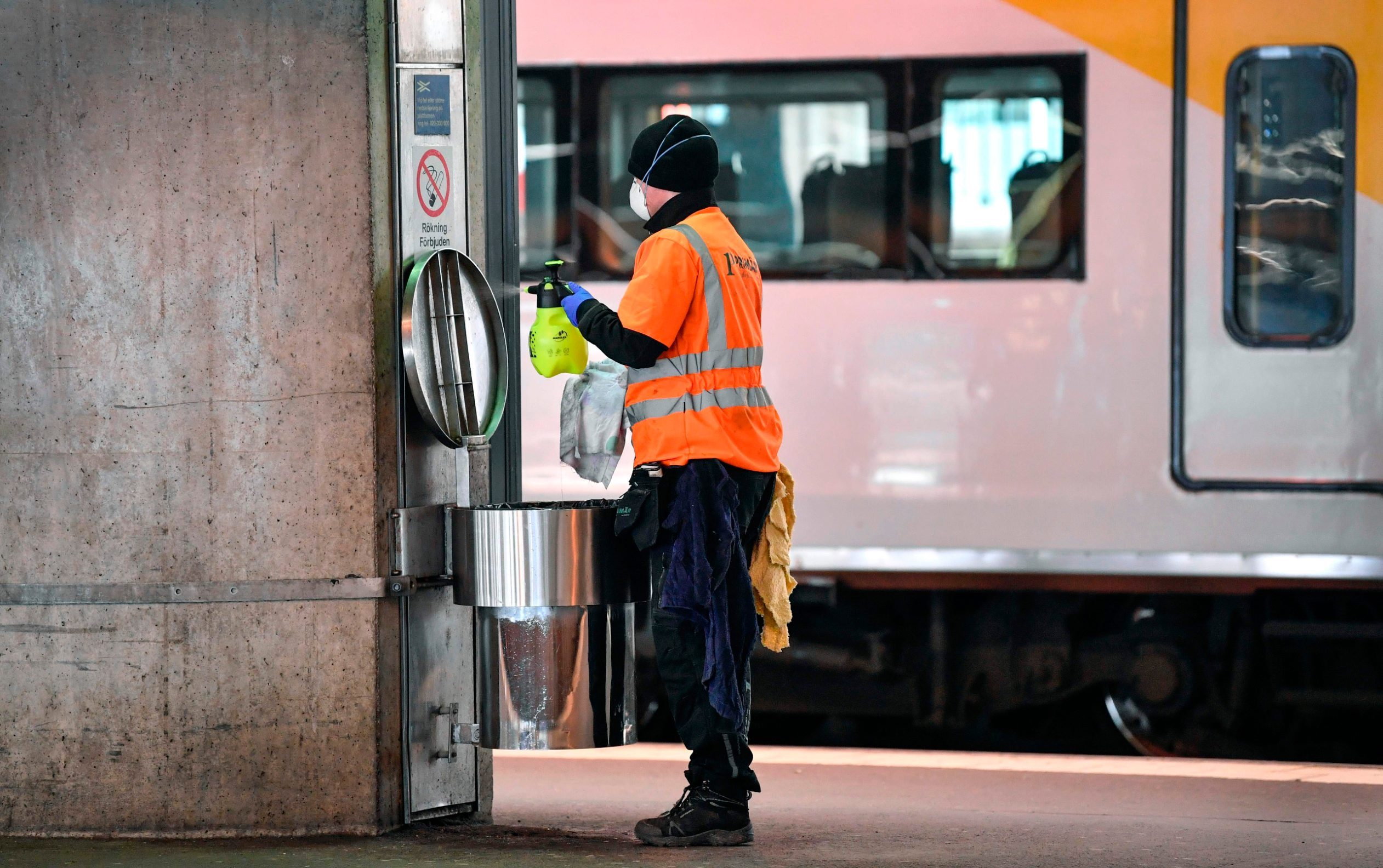A cleaner wearing a face mask cleans a wastepaper basket on a deserted platform for trains bound for Arlanda Airport, at Stockholm Central station on March 12, 2020 as very few passengers pass the Central station due to the Coronavirus Covid-19 outbreak. (Photo by Anders WIKLUND / various sources / AFP) / Sweden OUT