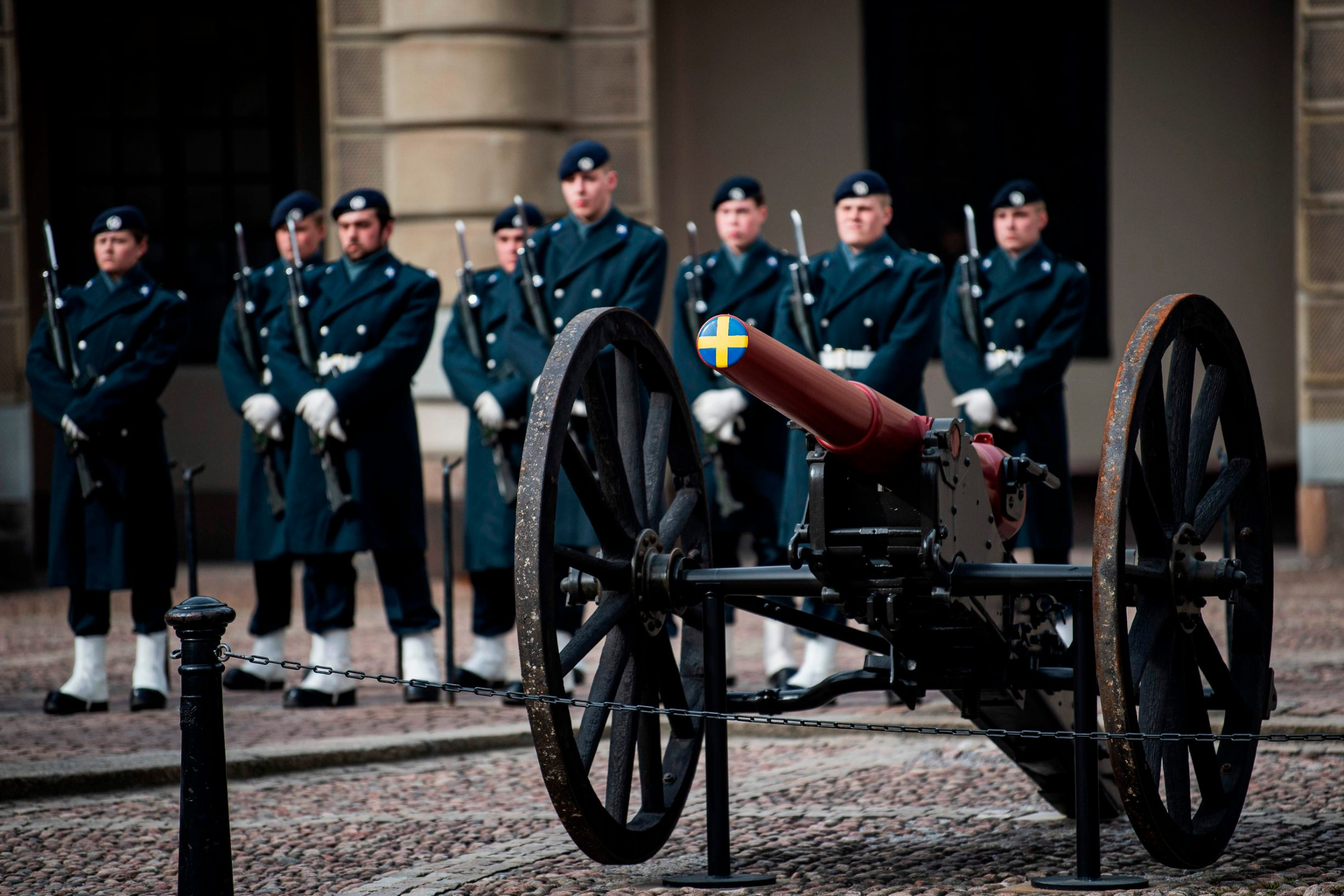Soldiers of the royal guard change shifts at the royal palace in Stockholm, Sweden, while the rest of Europe is in lockdown in a bid to curb the spread of the new coronavirus COVID-19, on March 25, 2020. - While most of Europe is firmly locked down in a bid to curb the spread of COVID-19, Sweden is taking a softer line, keeping primary schools, restaurants and bars open and even encouraging people to go outside for a nip of air. This stands in stark contrast to the urgent tone elsewhere and has sparked heated debate whether Sweden is really doing the right thing. (Photo by Jonathan NACKSTRAND / AFP)