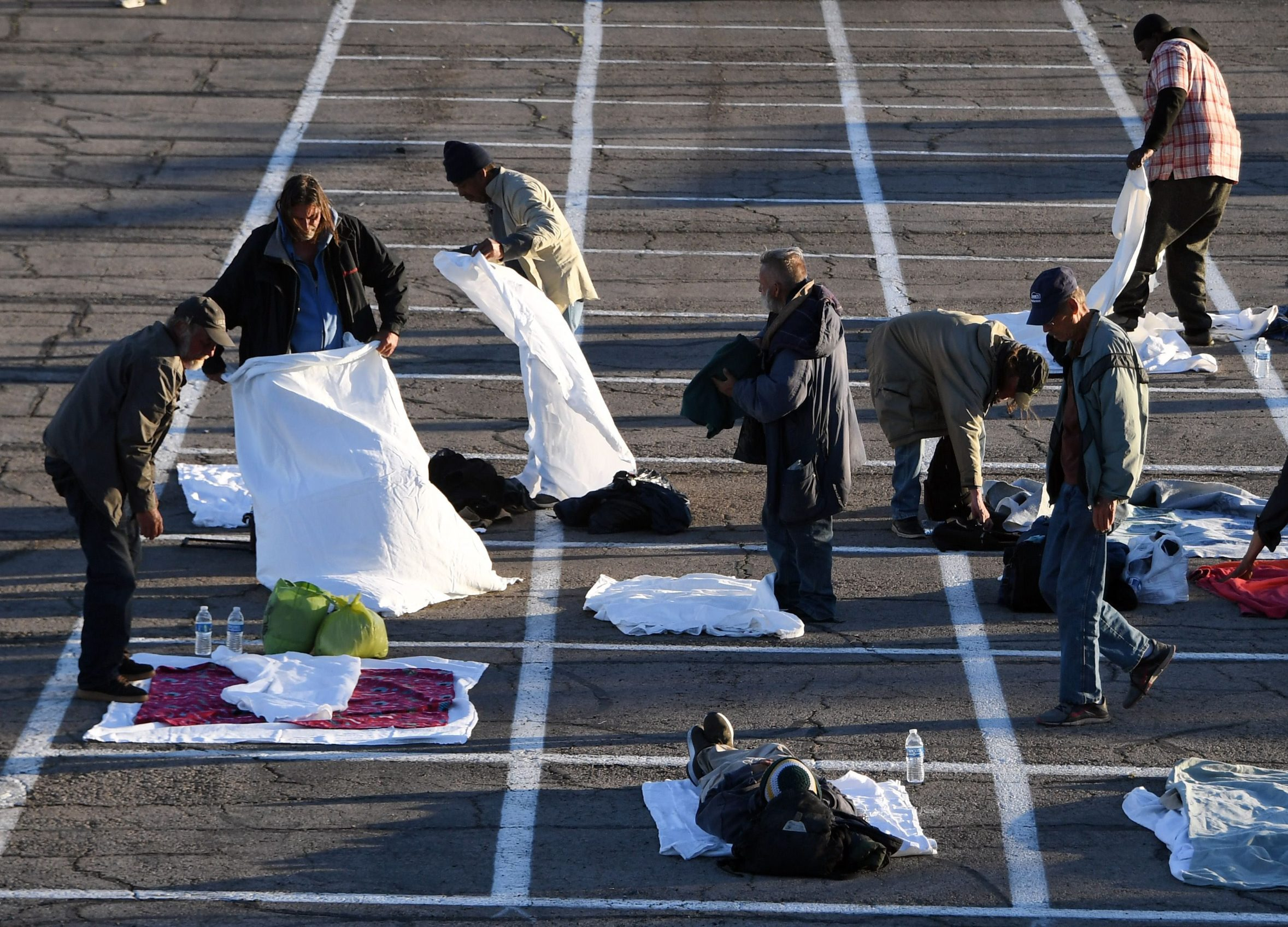 LAS VEGAS, NEVADA - MARCH 30: People arrive at a temporary homeless shelter set up in a parking lot at Cashman Center on March 30, 2020 in Las Vegas, Nevada. Catholic Charities of Southern Nevada was closed last week after a homeless man who used their services tested positive for the coronavirus, leaving about 500 people with no overnight shelter. The city of Las Vegas, Clark County and local homeless providers plan to operate the shelter through April 3rd when it is anticipated that the Catholic Charities facility will be back open. The city is also reserving the building spaces at Cashman Center in case of an overflow of hospital patients. The World Health Organization declared the coronavirus (COVID-19) a global pandemic on March 11th.   Ethan Miller/Getty Images/AFP == FOR NEWSPAPERS, INTERNET, TELCOS & TELEVISION USE ONLY ==