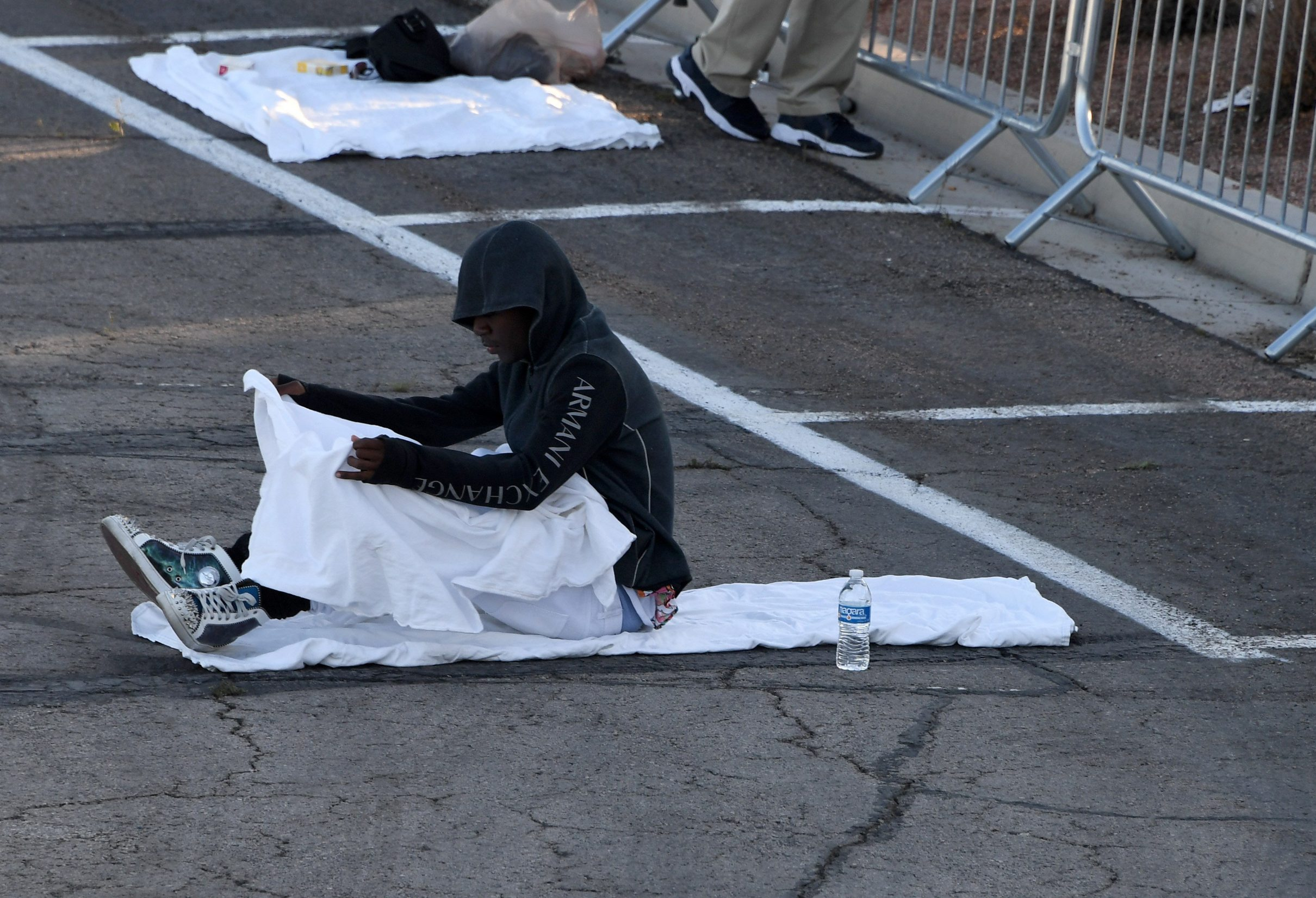 LAS VEGAS, NEVADA - MARCH 30: A man pulls a blanket over himself as he lies down at a temporary homeless shelter set up in a parking lot at Cashman Center on March 30, 2020 in Las Vegas, Nevada. Catholic Charities of Southern Nevada was closed last week after a homeless man who used their services tested positive for the coronavirus, leaving about 500 people with no overnight shelter. The city of Las Vegas, Clark County and local homeless providers plan to operate the shelter through April 3rd when it is anticipated that the Catholic Charities facility will be back open. The city is also reserving the building spaces at Cashman Center in case of an overflow of hospital patients. The World Health Organization declared the coronavirus (COVID-19) a global pandemic on March 11th.   Ethan Miller/Getty Images/AFP == FOR NEWSPAPERS, INTERNET, TELCOS & TELEVISION USE ONLY ==