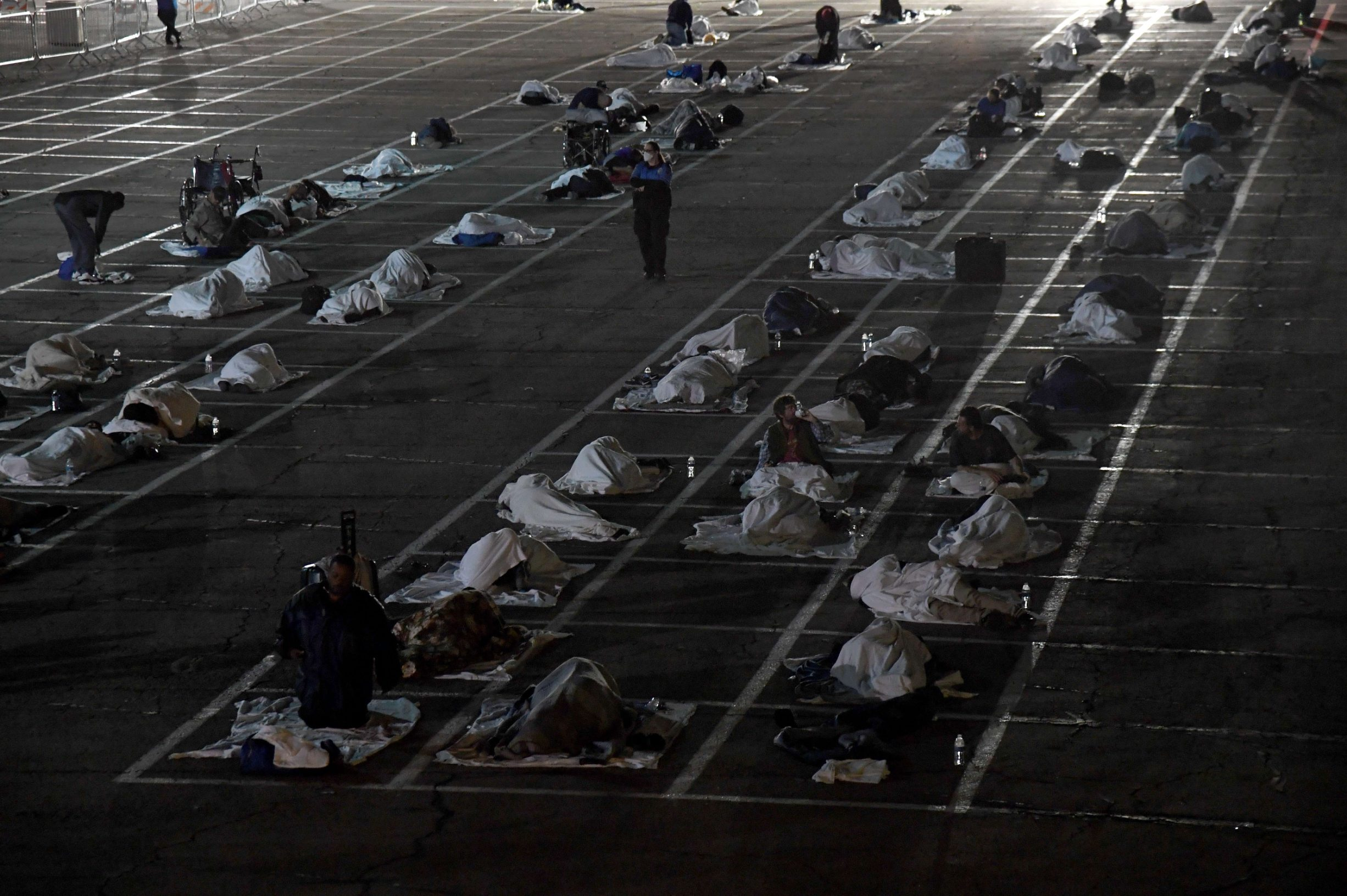 LAS VEGAS, NEVADA - MARCH 30: People sleep in social-distancing boxes at a temporary homeless shelter set up in a parking lot at Cashman Center on March 30, 2020 in Las Vegas, Nevada. Catholic Charities of Southern Nevada was closed last week after a homeless man who used their services tested positive for the coronavirus, leaving about 500 people with no overnight shelter. The city of Las Vegas, Clark County and local homeless providers plan to operate the shelter through April 3rd when it is anticipated that the Catholic Charities facility will be back open. The city is also reserving the building spaces at Cashman Center in case of an overflow of hospital patients. The World Health Organization declared the coronavirus (COVID-19) a global pandemic on March 11th.   Ethan Miller/Getty Images/AFP == FOR NEWSPAPERS, INTERNET, TELCOS & TELEVISION USE ONLY ==