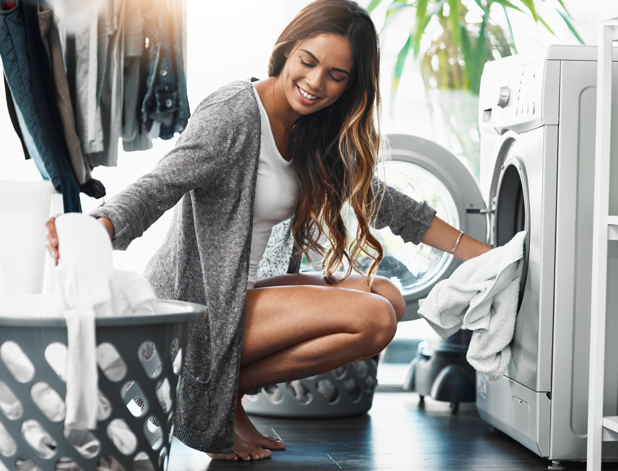 Full length shot of an attractive young woman doing her laundry at home