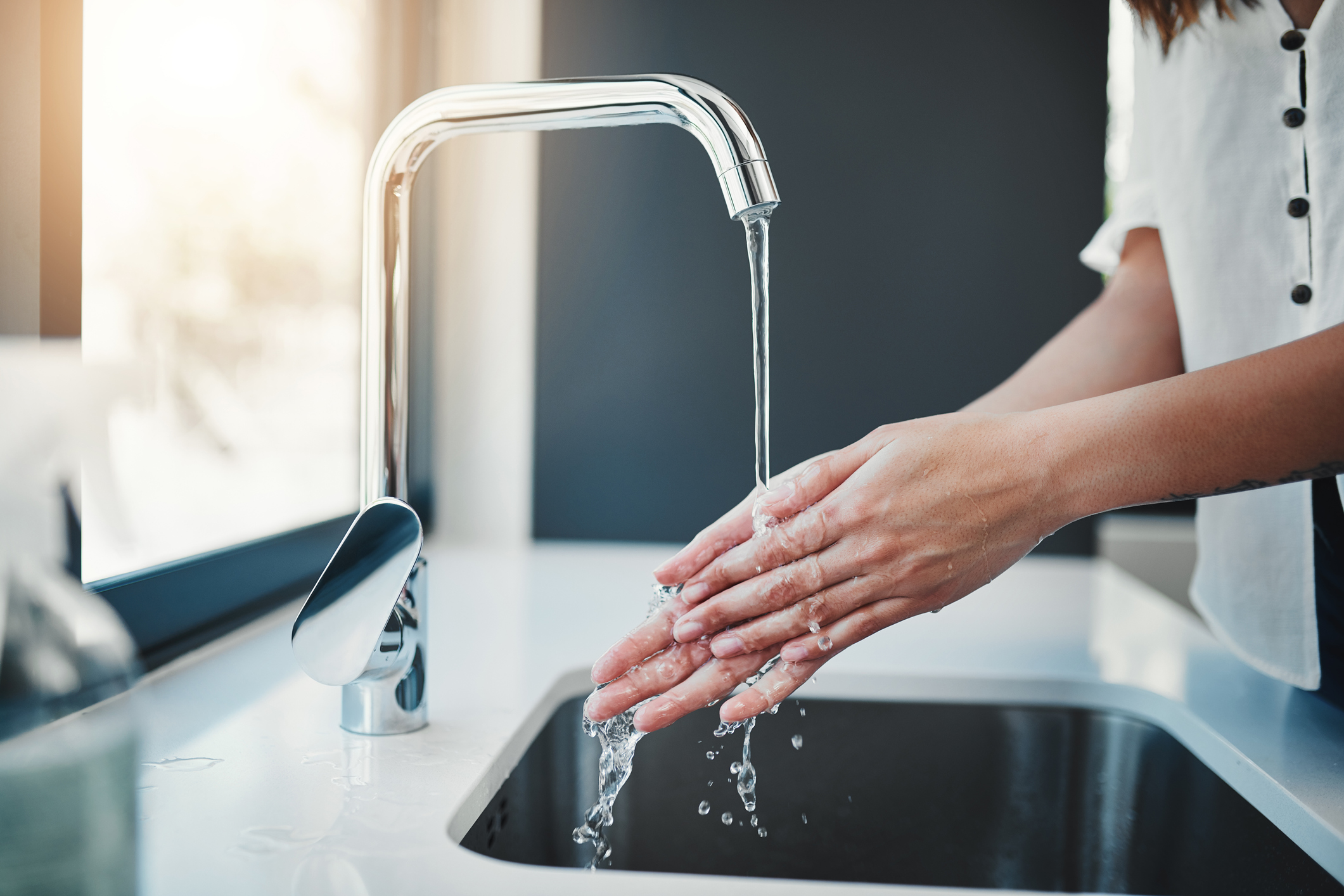 Cropped shot of an unrecognizable woman washing her hands in the kitchen sink