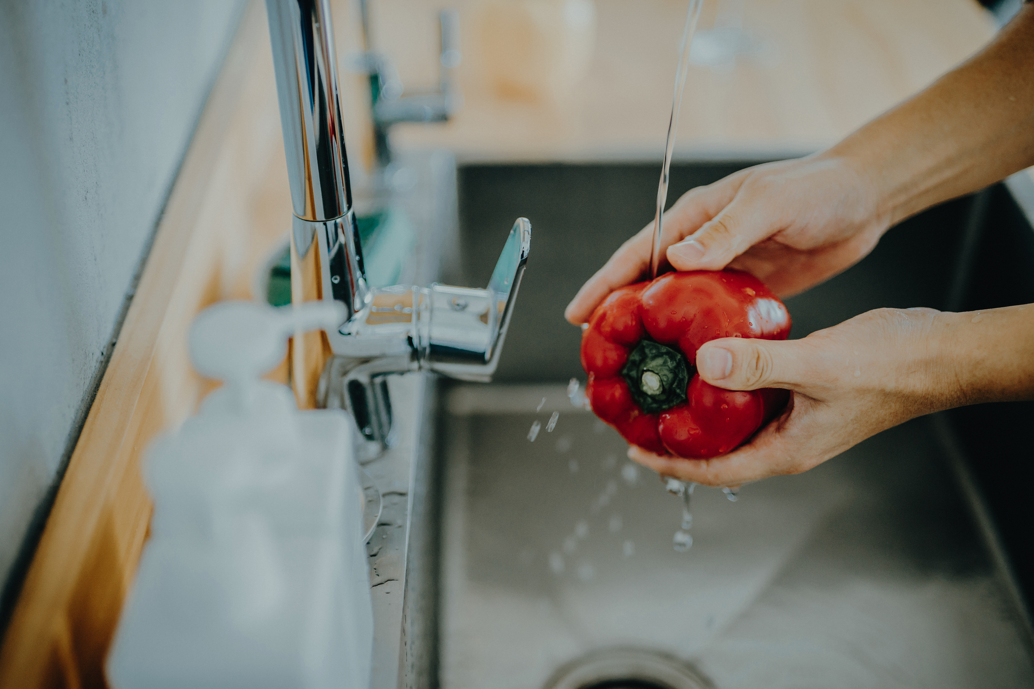 Close up of man's hand washing red bell pepper under running water in the kitchen