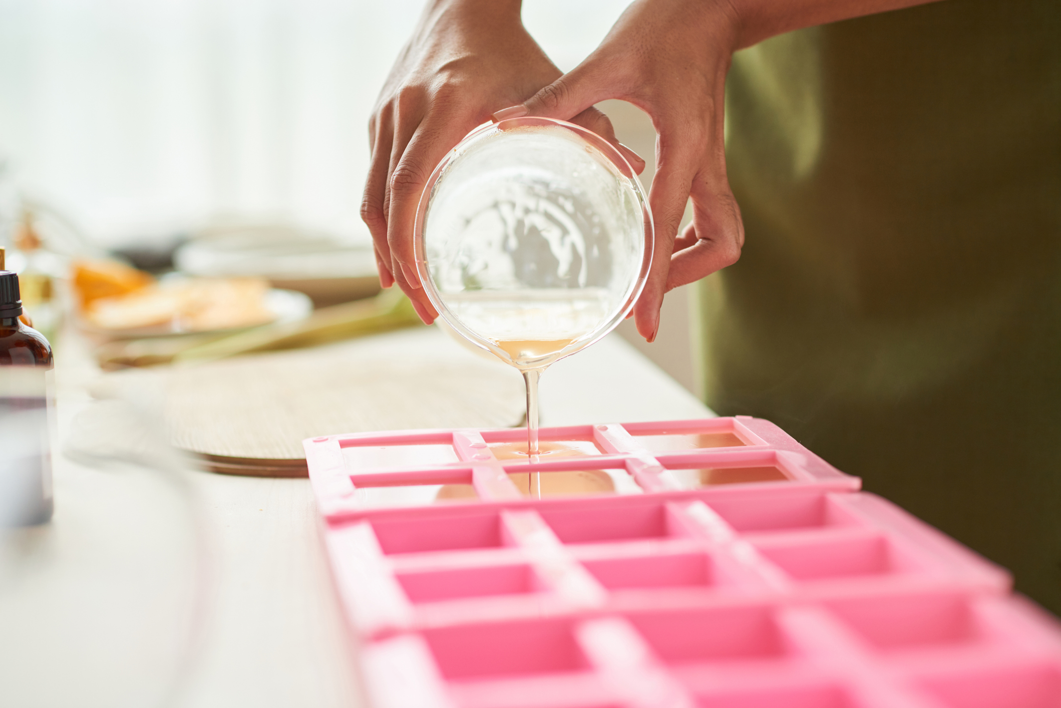Close-up image of woman pouring soap mixture into plastic form