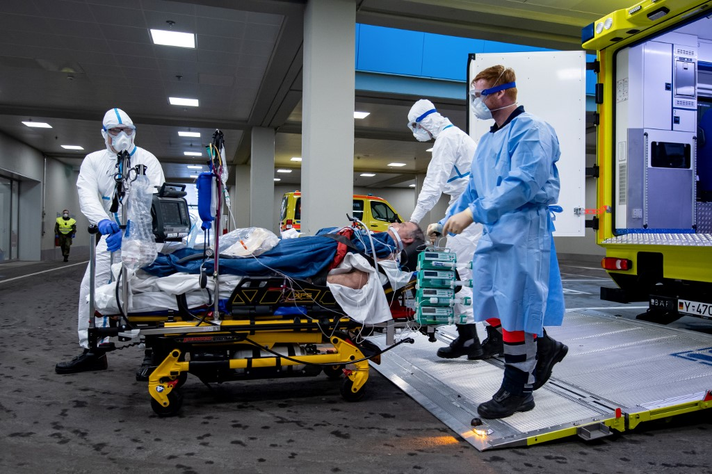 This handout photo made available by the German Bundeswehr armed forces shows medical staff transporting a French patient infected with the novel coronavirus from an ambulance car to the intensive care ward of the Bundeswehrkrankenhaus hospital of the German armed forces Bundeswehr in Ulm, southwestern Germany, after the patient was flown in from France to get medical treatment, on March 29, 2020. (Photo by Bjoern HOSSFELD / BUNDESWEHR / AFP) / RESTRICTED TO EDITORIAL USE - MANDATORY CREDIT