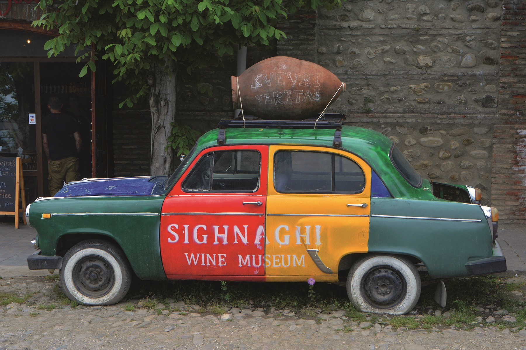Advertising for the Wine Museum in the city of Sighnaghi (Signagi) in Georgia (Kakheti) on a discarded vintage Soviet car - the region is known for traditional wine growing, recorded on 21.05.2019 | usage worldwide