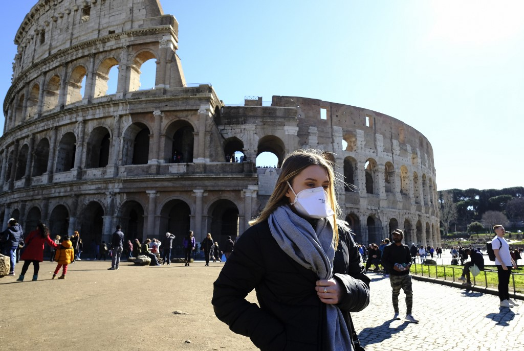 Tourist wearing a protective respiratory mask tours outside the Colosseo monument (Colisee, Coliseum) in downtown Rome on February 28, 2020 amid fear of Covid-19 epidemic. - Since February 23, more than 50,000 people have been confined to 10 towns in Lombardy and one in Veneto -- a drastic measure taken to halt the spread of the new coronavirus, which has infected some 400 people in Italy, mostly in the north. (Photo by Andreas SOLARO / AFP)
