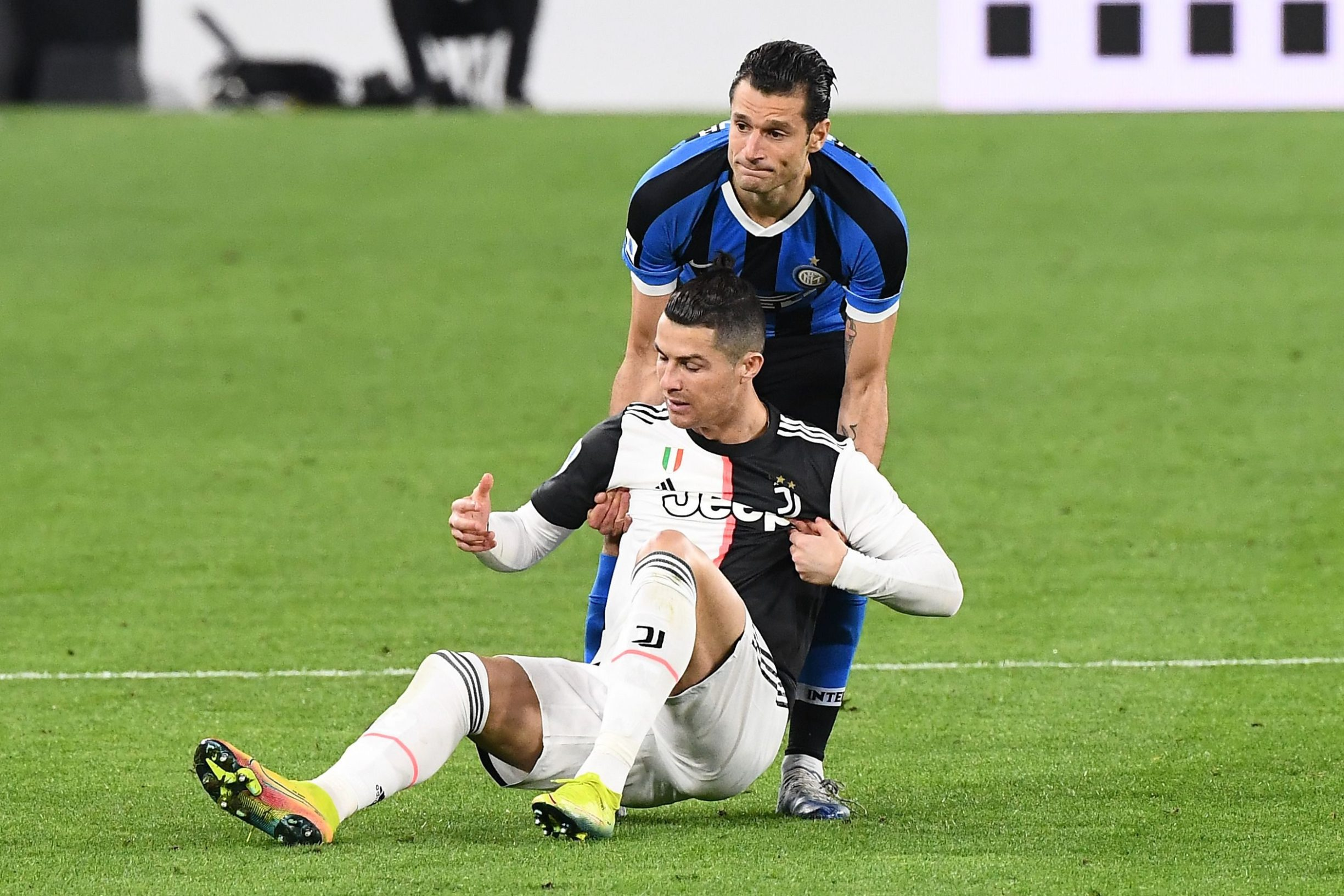 Juventus' Portuguese forward Cristiano Ronaldo (front) is helped by Inter Milan's Italian forward Antonio Candreva to stand up during the Italian Serie A football match Juventus vs Inter Milan, at the Juventus stadium in Turin on March 8, 2020. - The match is played behind closed doors due to the novel coronavirus outbreak. (Photo by Vincenzo PINTO / AFP)