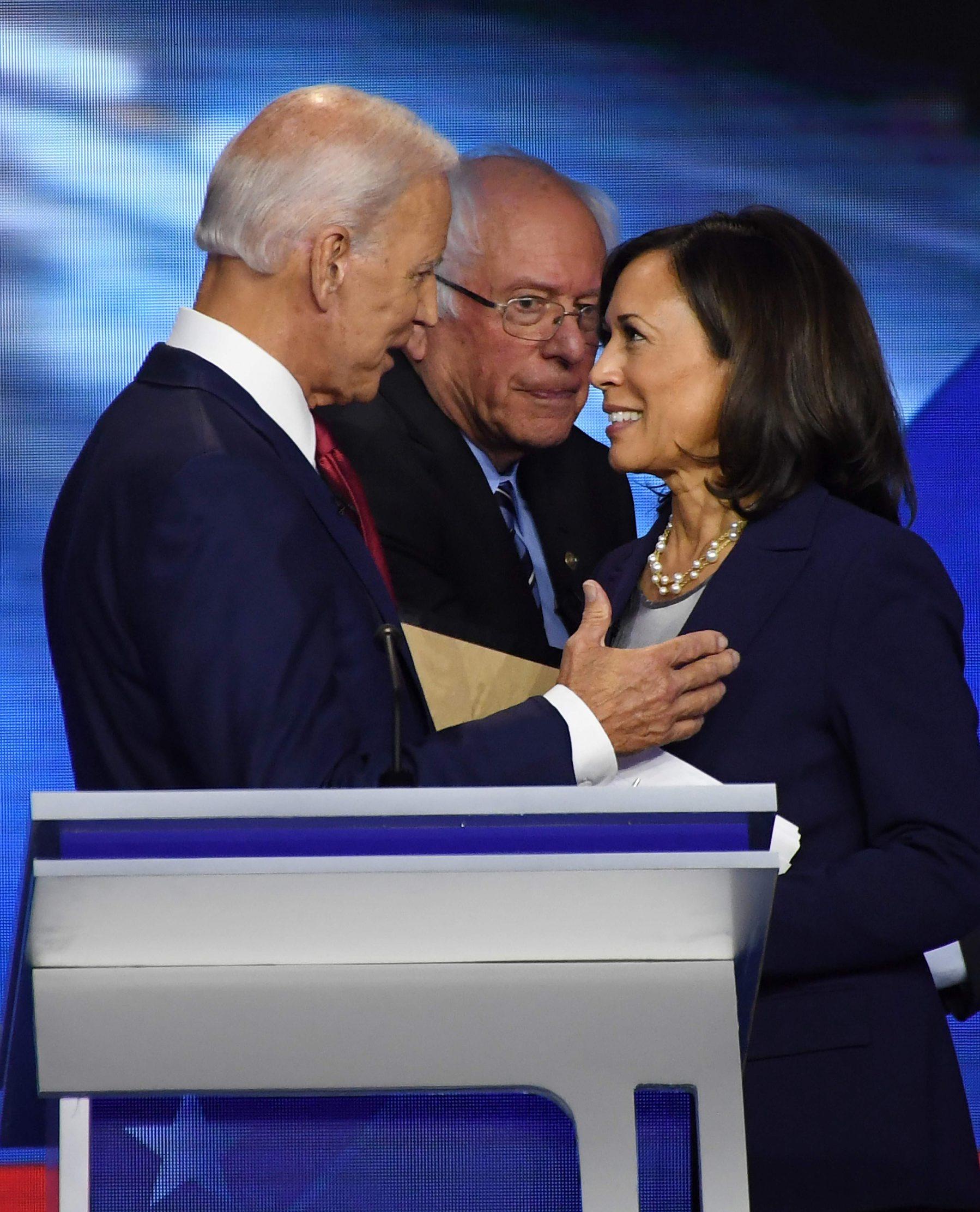 Na slici demokratski kandidat Joe Biden (lijevo) i senatorica Kamala Harris (desno) dok u pozadini prolazi demokratski kandidat Bernie Sanders