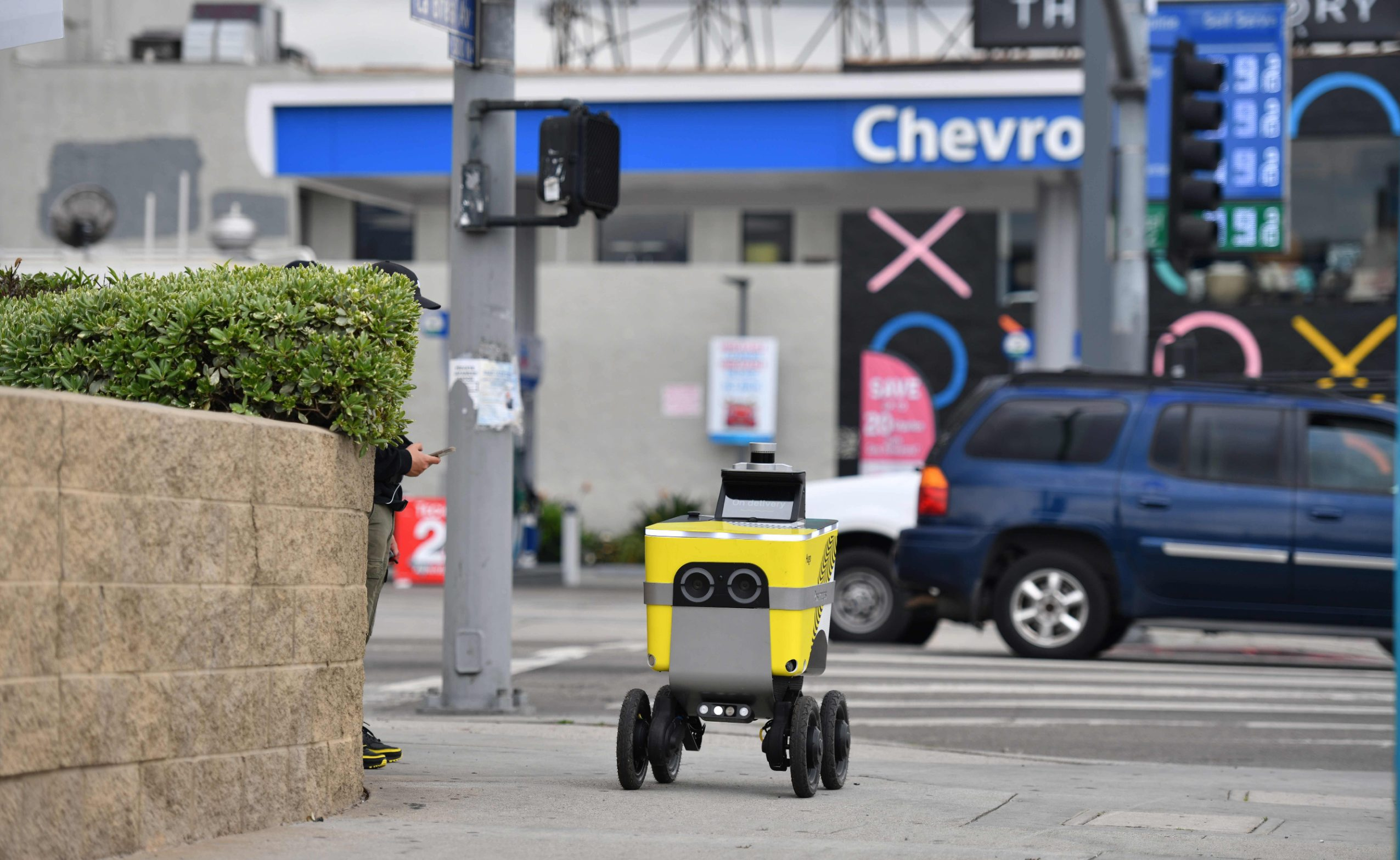 A Postmate delivery robot is seen on its route to deliver food to customers in Los Angeles on March 24, 2020. - In California, already under orders to stay home, Governor Gavin Newsom tightened the lockdown to shut parking lots at beaches and parks after tens of thousands flouted social distancing rules. (Photo by Chris DELMAS / AFP)