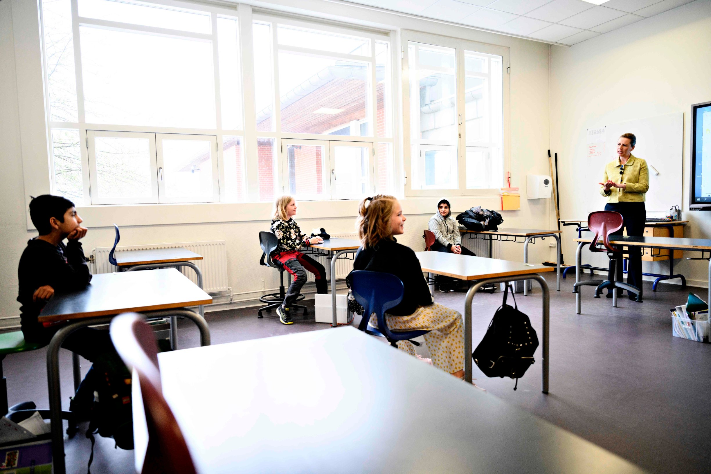 Danish Prime Minister Mette Frederiksen (R) speaks with pupils as she participates in the reopening of Lykkebo School in Valby in Copenhagen on April 15, 2020, after the lockdown to limit the spread of the new coronavirus. - Denmark began reopening schools after a month-long closure over the novel coronavirus, becoming the first country in Europe to do so. Nurseries, kindergartens and primary schools were reopening, according to an AFP correspondent, after they were closed on March 12, 2020 in an effort to curb the COVID-19 epidemic. (Photo by Philip Davali / Ritzau Scanpix / AFP) / Denmark OUT