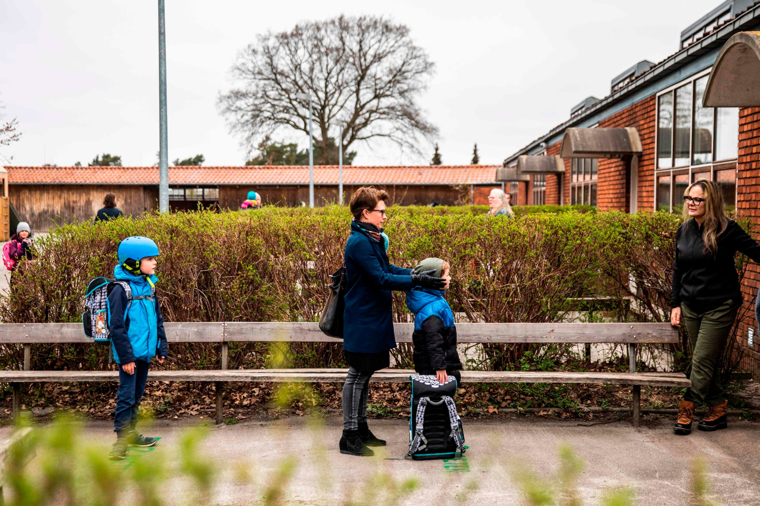 Parents with their children stand in queue waiting to get inside Stengaard School north of Copenhagen, Denmark, on April 15, 2020, after the new coronavirus lockdown. - Denmark began reopening schools on April 15, 2020 for younger children after a month-long closure over the novel coronavirus, becoming the first country in Europe to do so. Nurseries, kindergartens and primary schools were reopening, according to an AFP correspondent, after they were closed on March 12, 2020 in an effort to curb the COVID-19 pandemic. (Photo by Ólafur Steinar Gestsson / Ritzau Scanpix / AFP) / Denmark OUT