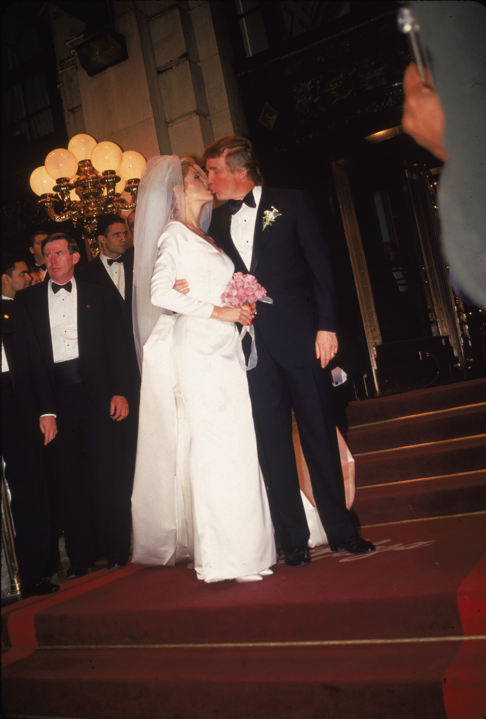 American businessman Donald Trump kisses his new bride Marla Maples following their wedding ceremony at Trump Plaza hotel, New York City, December 19, 1993. (Photo by Hulton Archive/Getty Images)