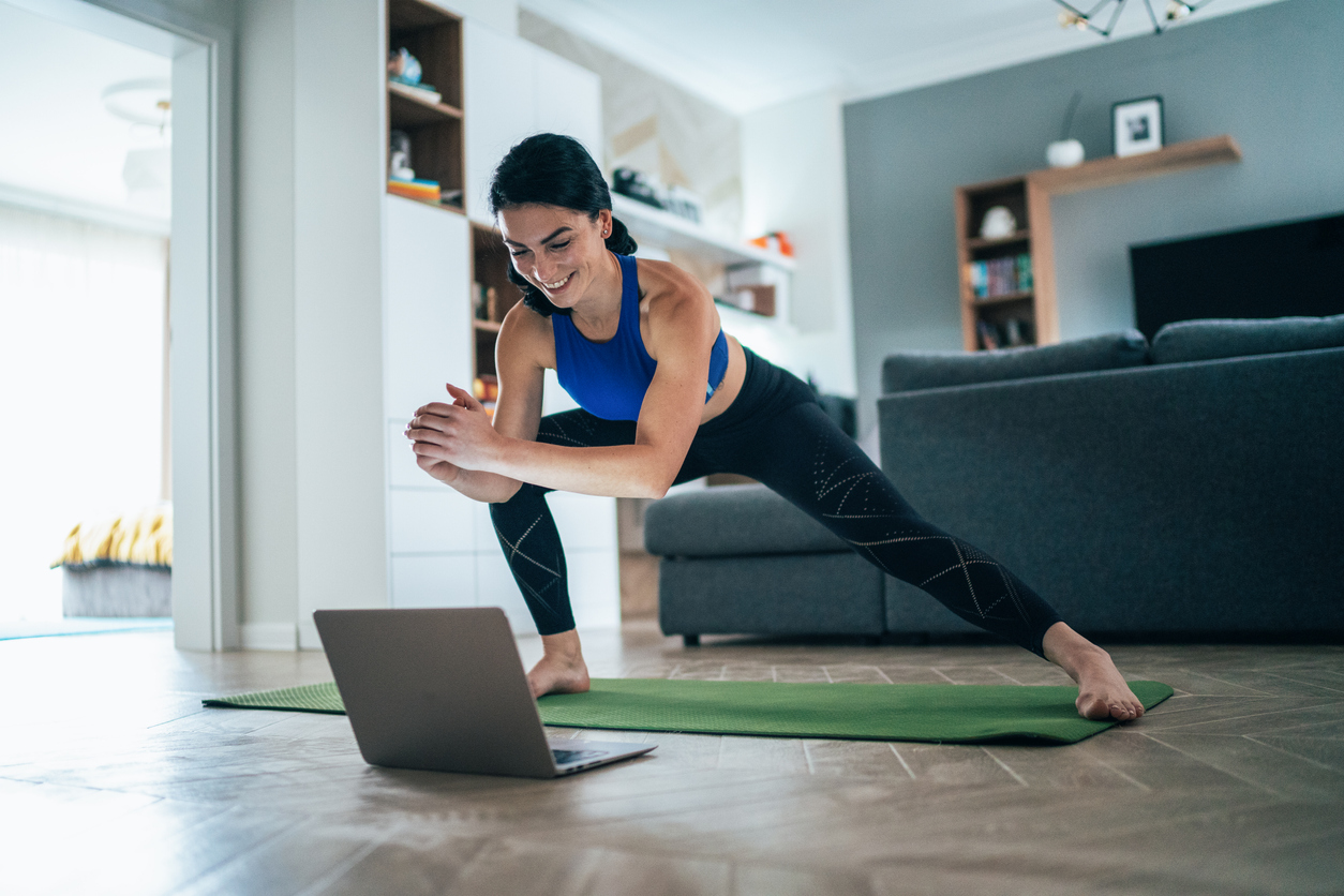 Fit woman doing side lunges indoors in a flat