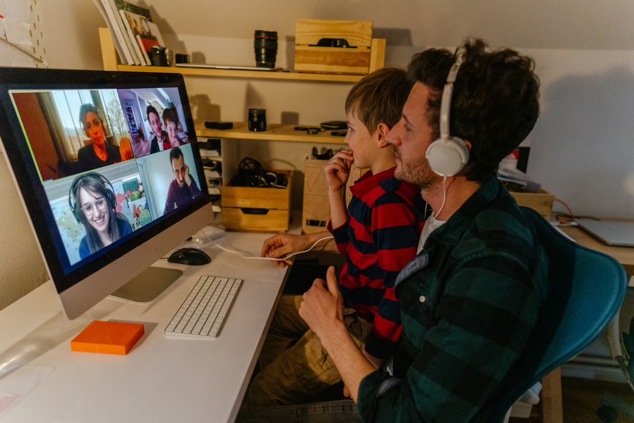 Photo of a man and his son having a video call with friends