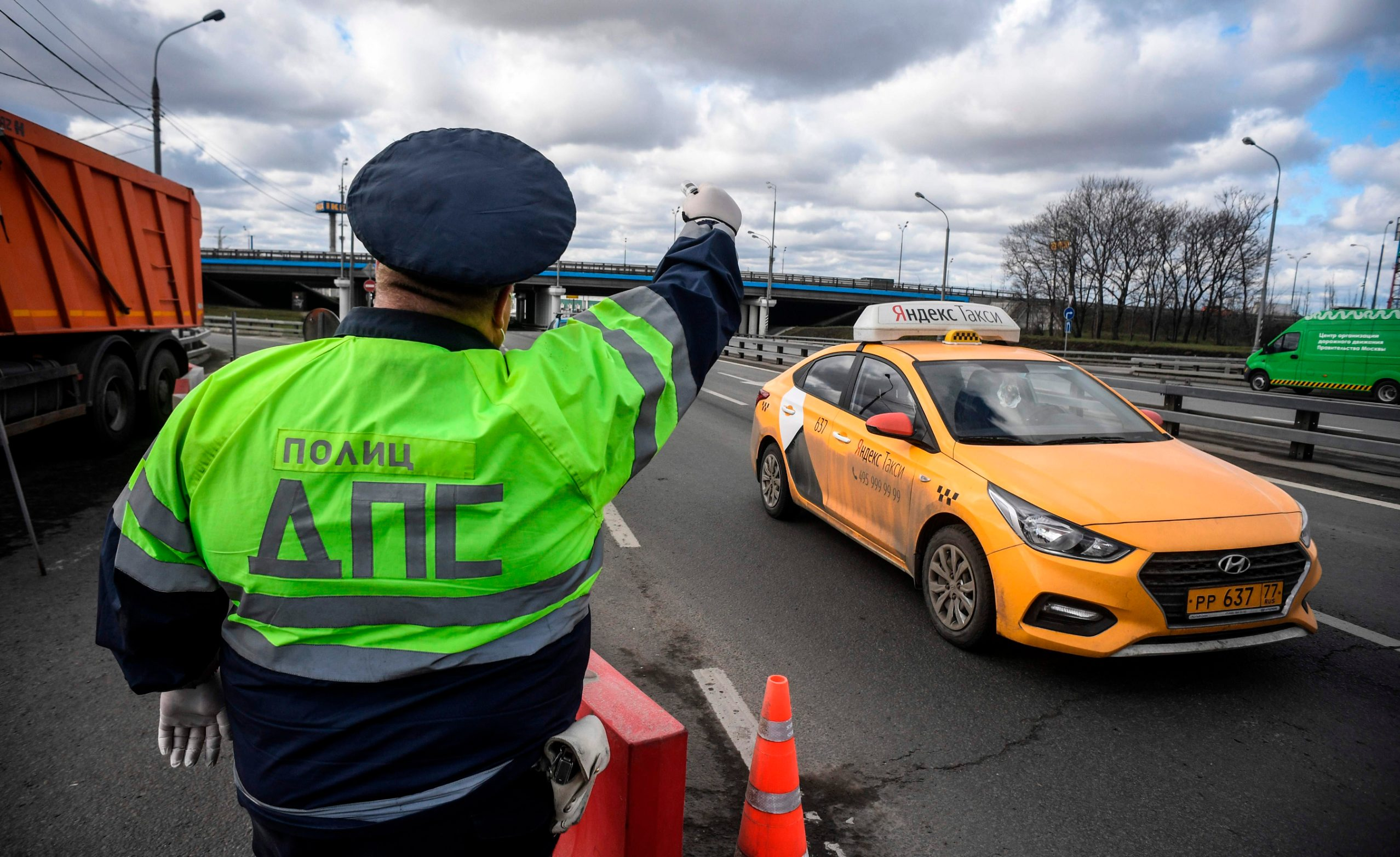 A traffic police officer stops a taxi to check IDs and passes of a driver and a passenger after the city authorities introduced a mandatory permit system for people travelling across the city by car or public transport in a bid to stop the spread of the COVID-19 coronavirus, at a checkpoint on the outskirts of Moscow on April 15, 2020. (Photo by Alexander NEMENOV / AFP)