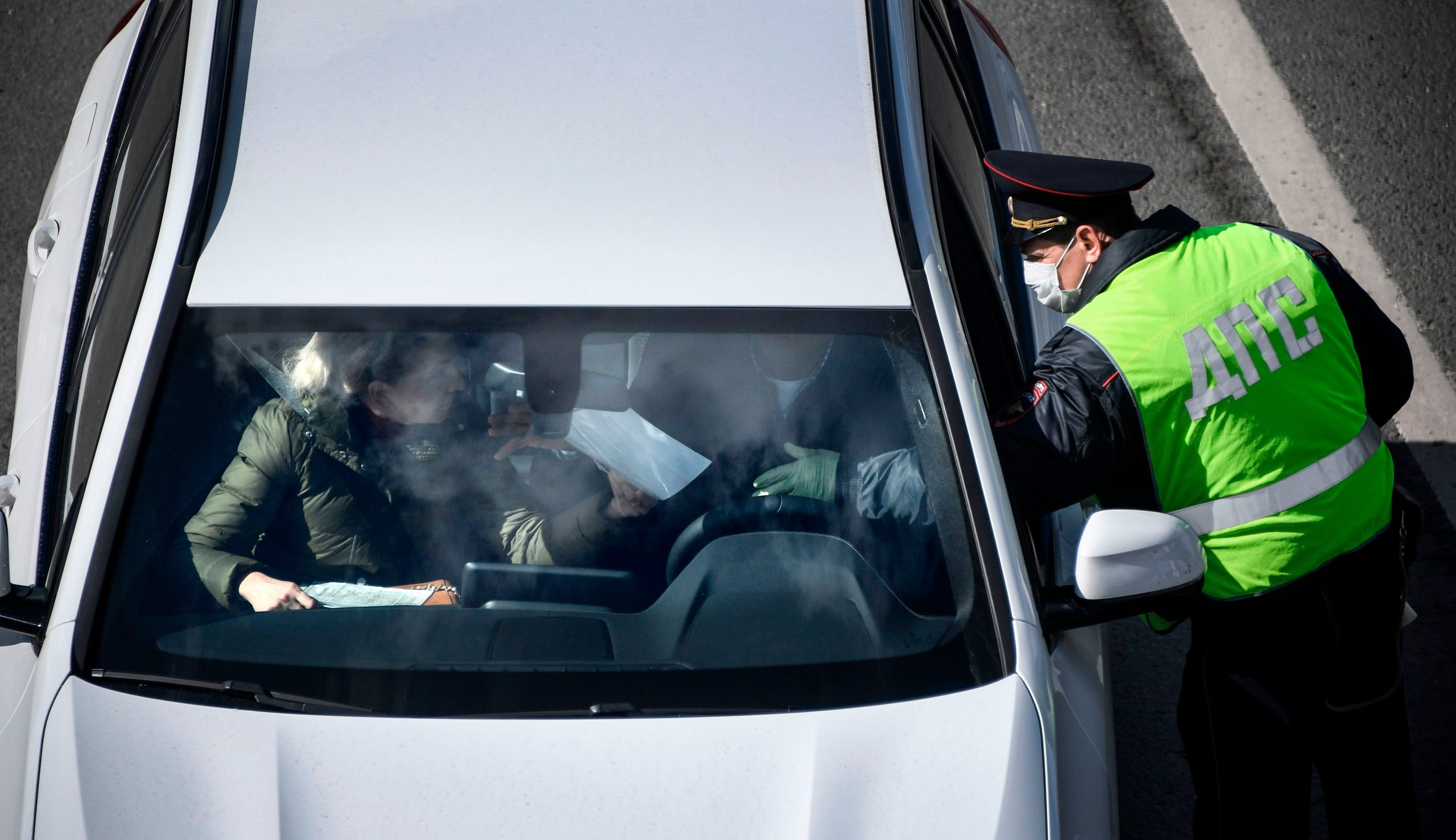 Traffic police check IDs and passes of drivers and passengers in cars entering Moscow after the city authorities introduced a mandatory permit system for people travelling across the city by car or public transport in a bid to stop the spread of the COVID-19 coronavirus, at a checkpoint on the outskirts of Moscow on April 15, 2020. (Photo by Alexander NEMENOV / AFP)