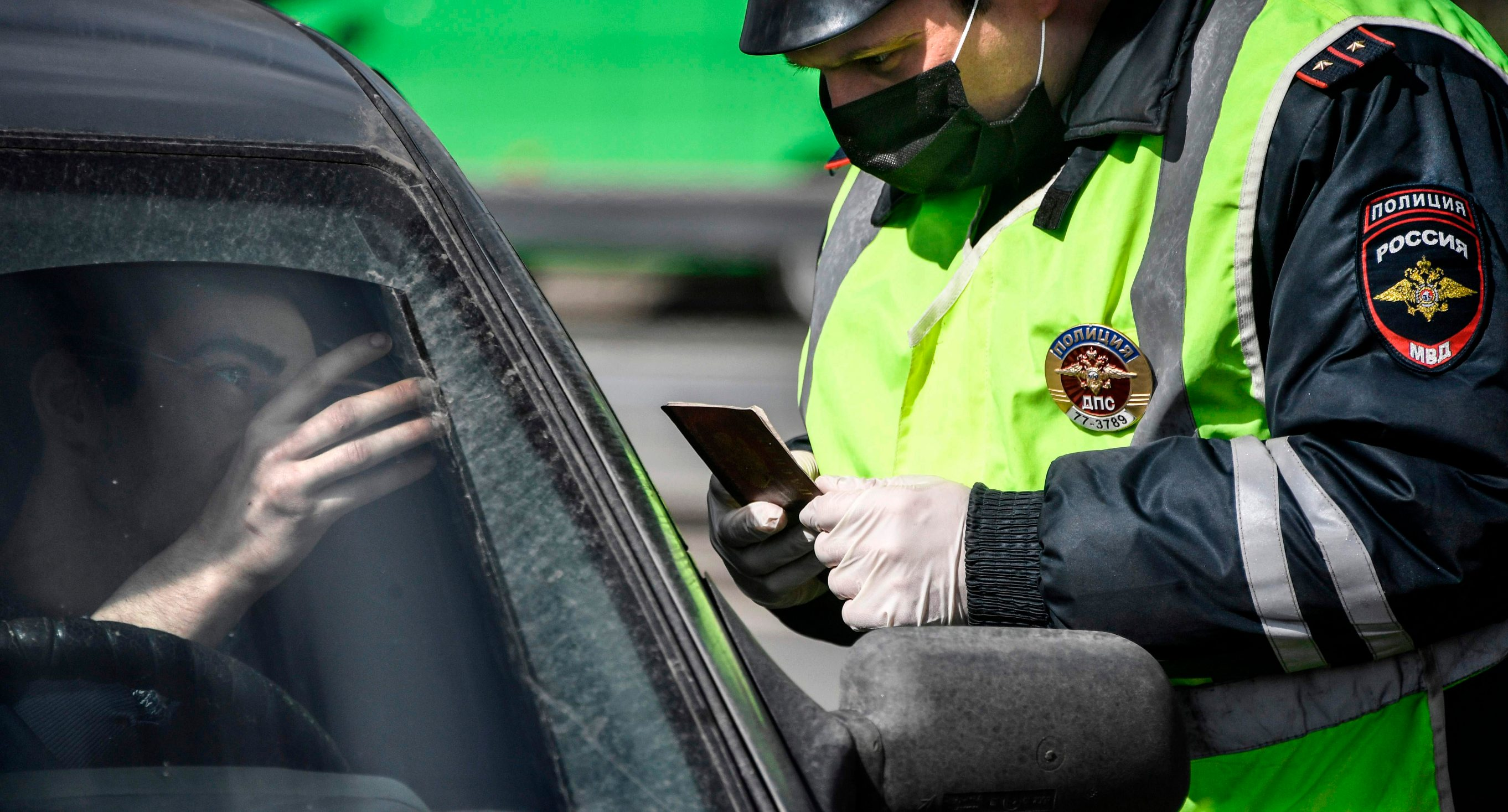 A traffic police officer checks an ID and a pass of a driver at a checkpoint on the outskirts of Moscow after the city authorities introduced a mandatory permit system for people travelling across the city by car or public transport in a bid to stop the spread of the COVID-19 coronavirus, on April 15, 2020. (Photo by Alexander NEMENOV / AFP)