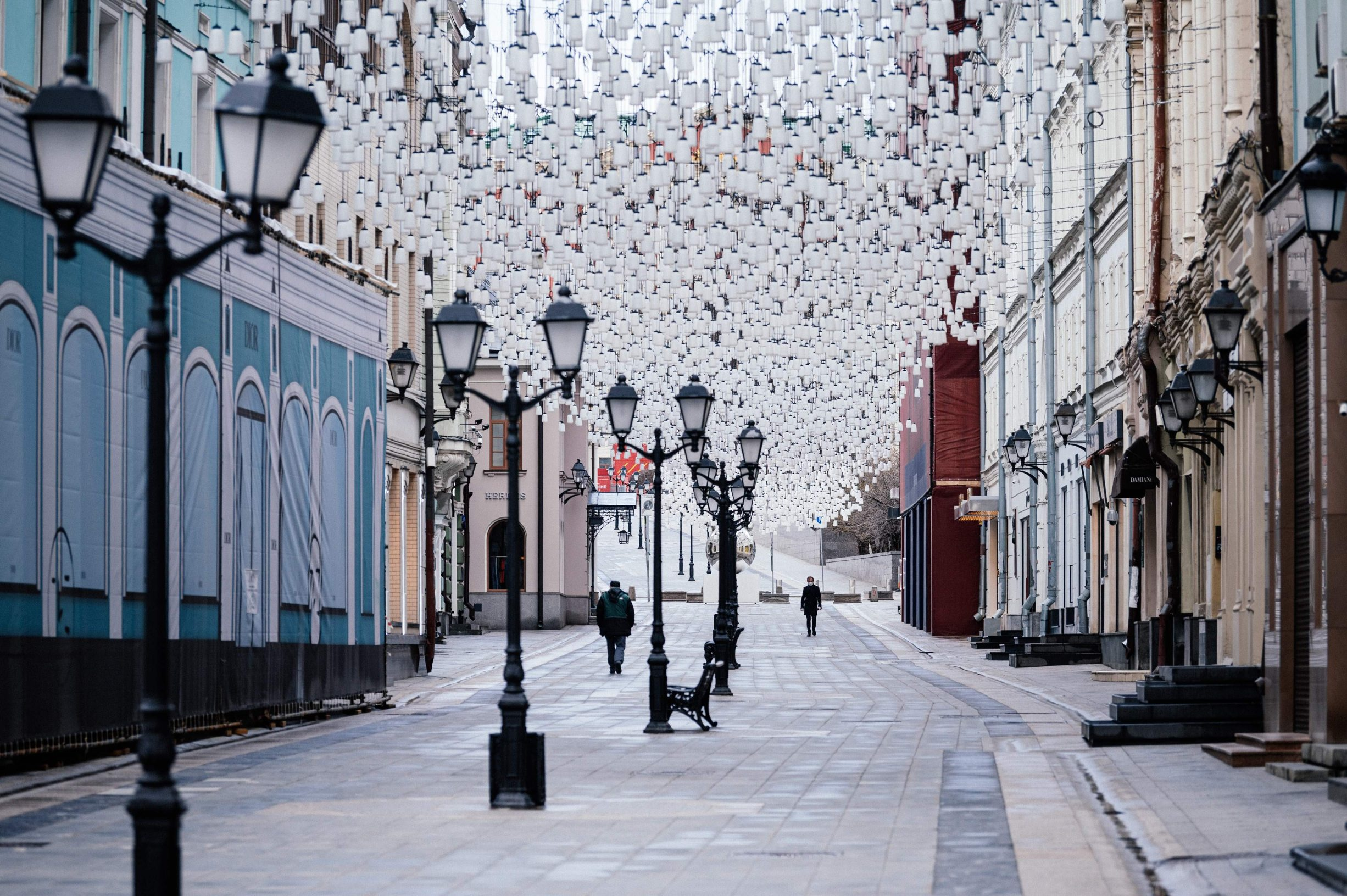 Rare pedestrians walk along Stoleshnikov lane in downtown Moscow on April 16, 2020, during a strict lockdown in Russia to stop the spread of the novel coronavirus COVID-19. (Photo by Dimitar DILKOFF / AFP)