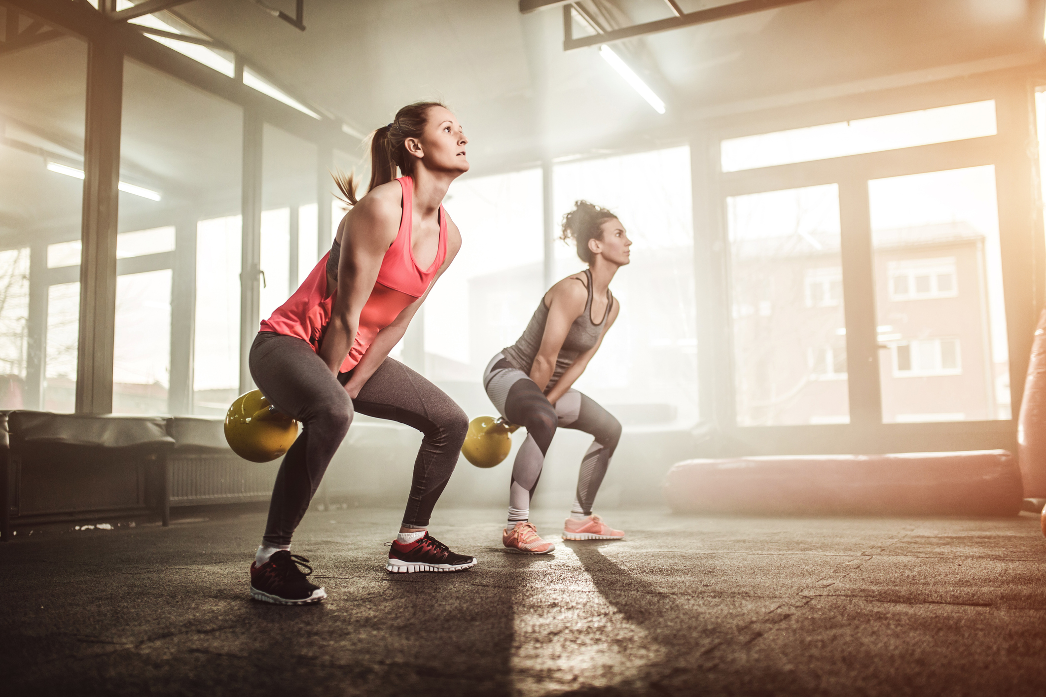 Two woman lifting kettle bell in gym gym