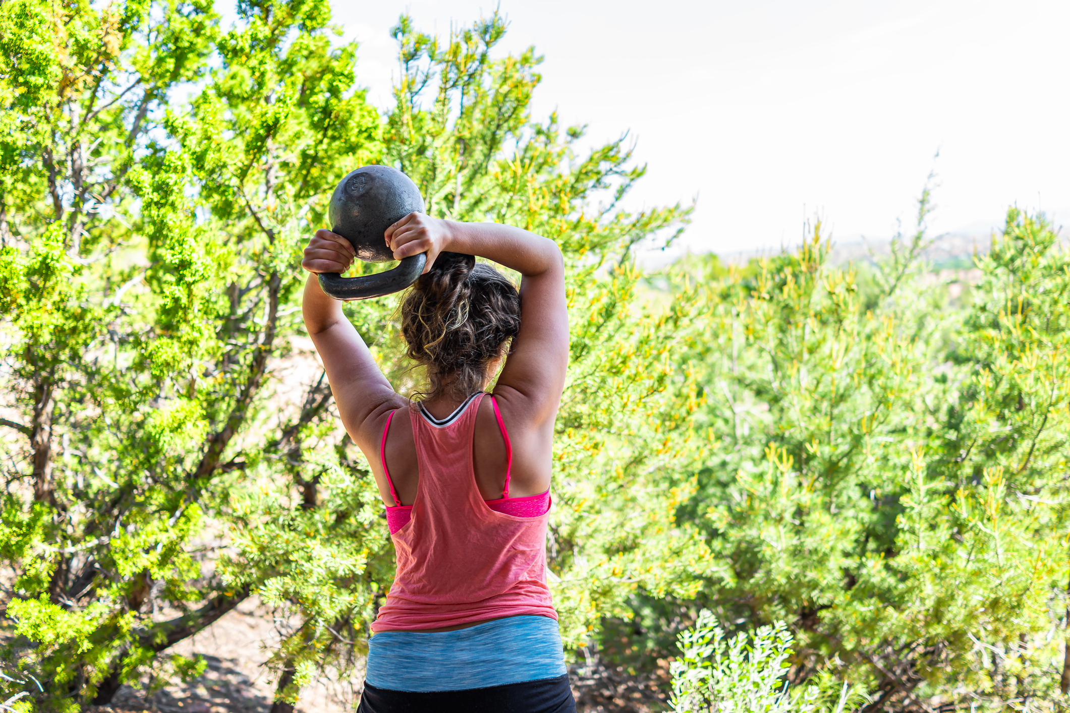 Back of young fit woman with heavy kettlebell doing triceps exercise and muscles in outdoors outside park holding weight lifting