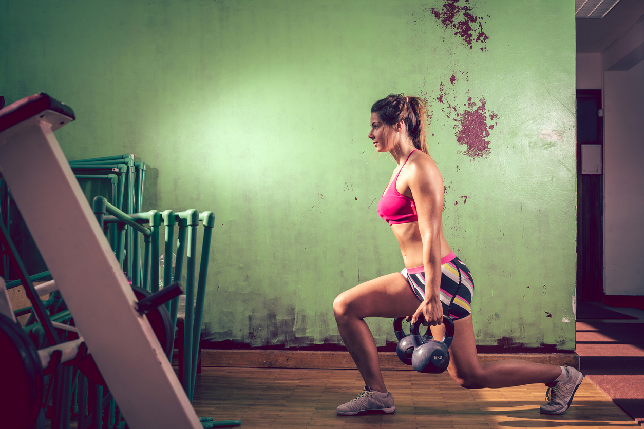 Young adult caucasian girl doing lunge exercise indoor with kettlebell. Toned image.