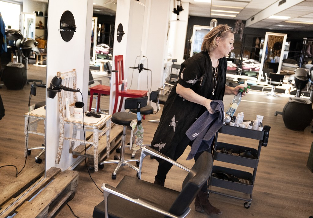 Christel Lerche at Hairdresser Hot N Tot reopens and welcomes the first customers, in Bagsvaerd near Copenhagen, April 20, 2020, amid the new coronavirus COVID-19 pandemic. - There is a pause before and after each customer and the hairdressers have permanent workstations. Customers wait for a good distance and every plastic shackle for customers' outerwear is thrown in the trash after use. Parts of Europe hit hard by the deadly coronavirus pandemic took tentative steps towards resuming normal lives on April 20, 2020. (Photo by Liselotte Sabroe / Ritzau Scanpix / AFP) / Denmark OUT