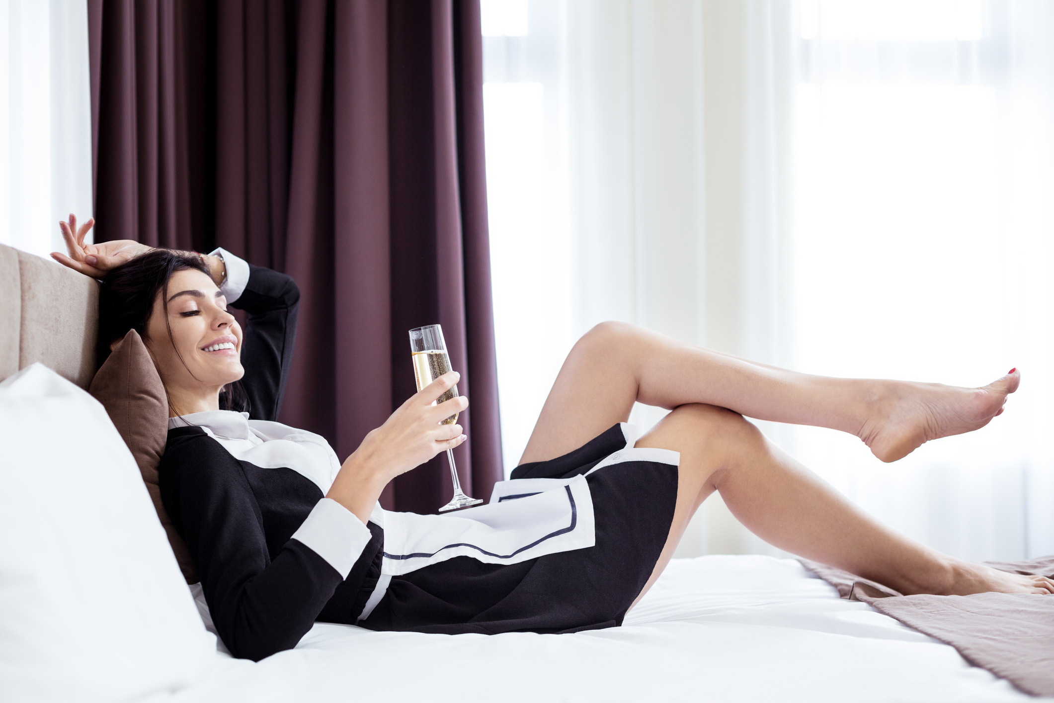Instead of work. Positive female hotel maid resting on the bed while not wanting to work