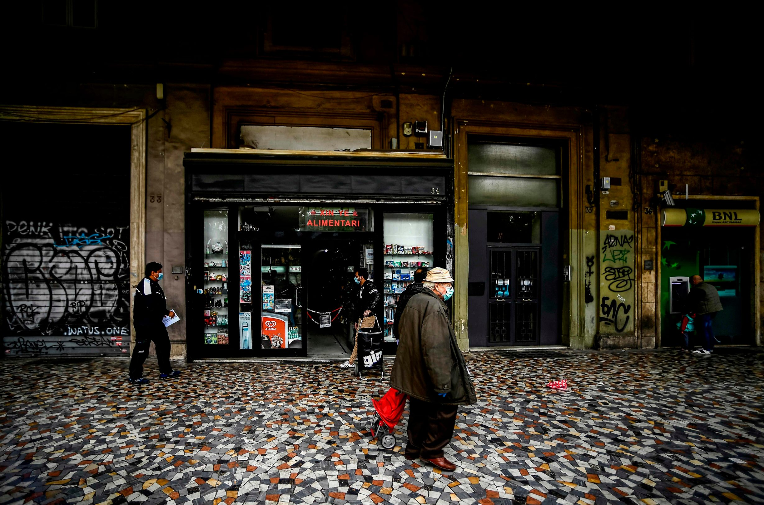 People wearing a face mask walk past a grocery shop as a man draws cash from an ATM (Rear R) on April 21, 2020 in Rome, during the lockdown aimed at curbing the spread of the COVID-19 infection, caused by the novel coronavirus. (Photo by Filippo MONTEFORTE / AFP)