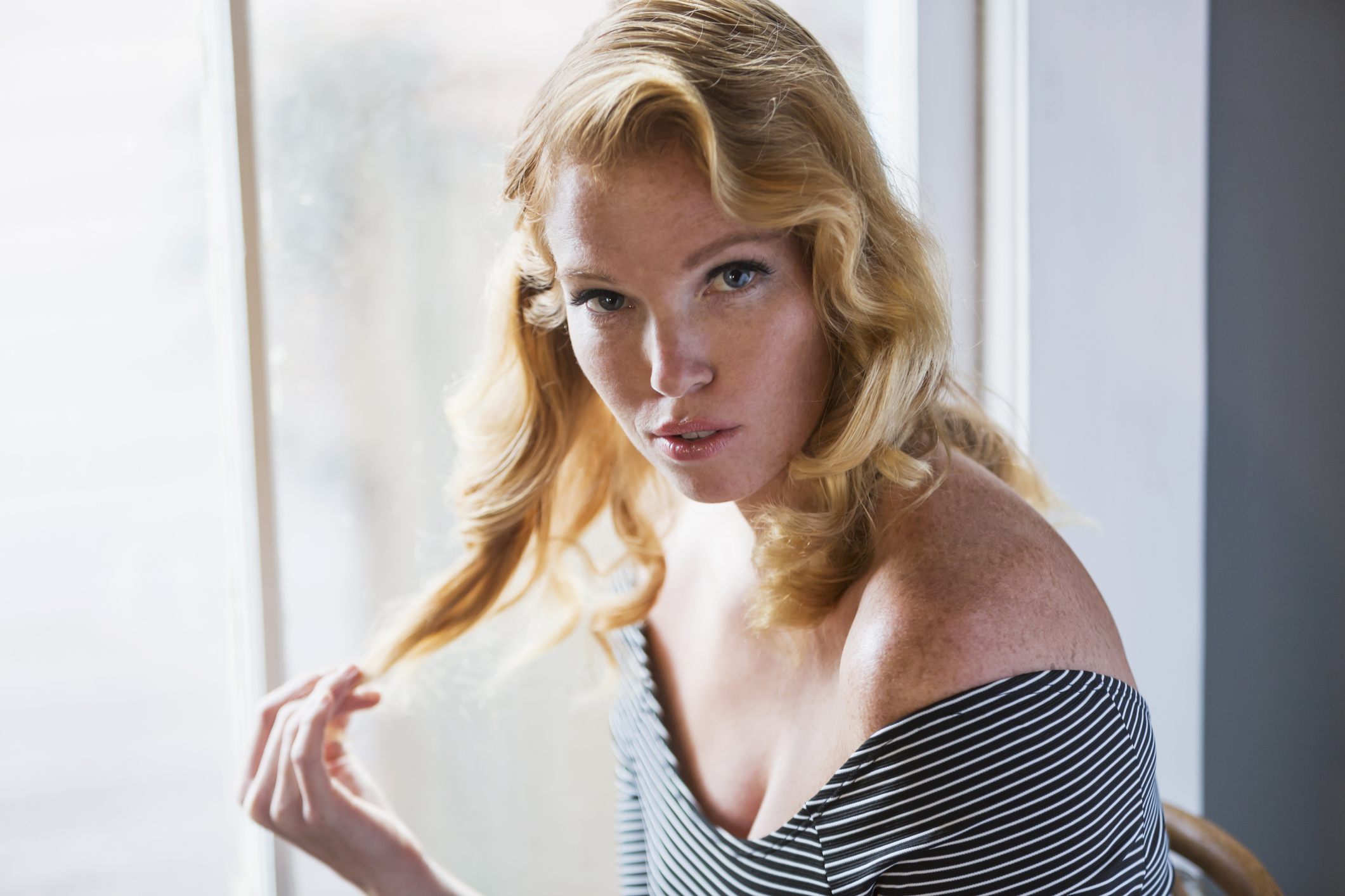 Seductive young blonde woman sitting indoors by sunny window, staring at the camera, playing with her hair.