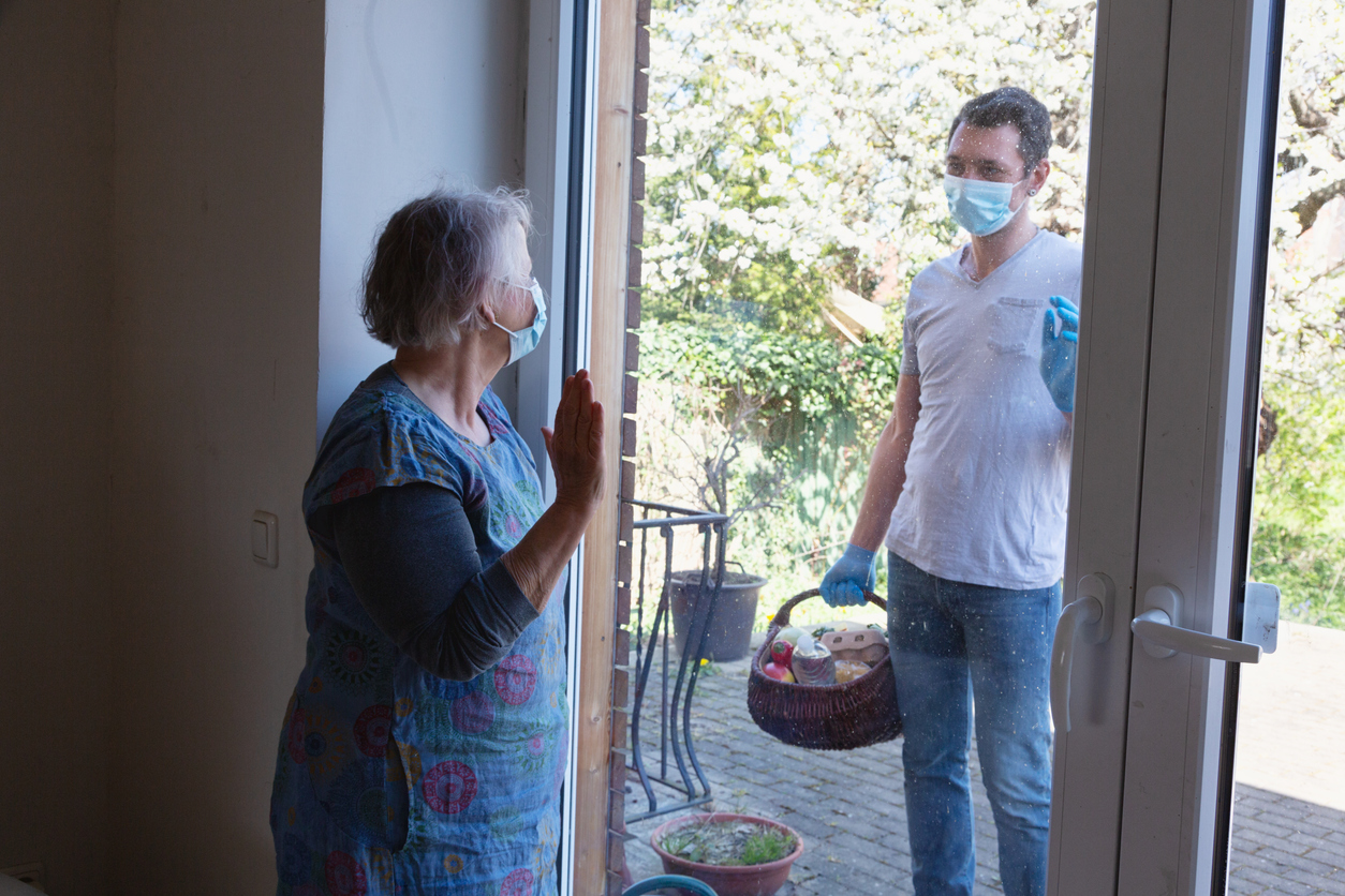Senior woman, 66 years old, wearing a blue dress, protectiver face mask and gloves, standing by the window and watching a man, a male volunteer  who is delivering a basket with groceries in times of COVID-19, he is wearing mask and gloves, too.