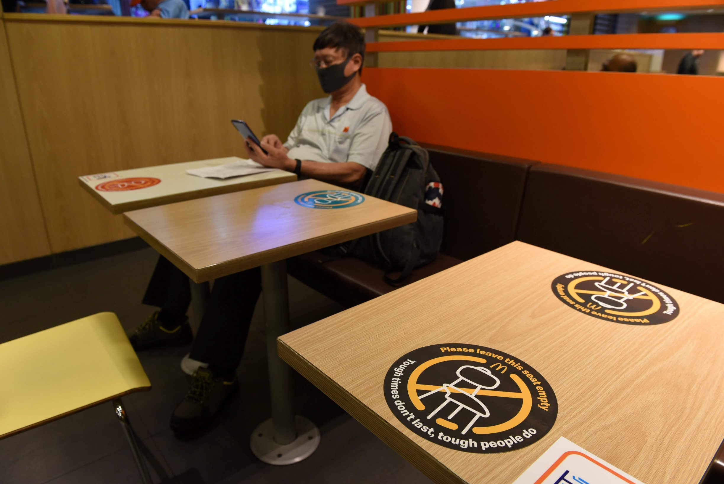A notice signage, as a preventive measure against the COVID-19 novel coronavirus, is posted on a restaurant table as authorities implement social distancing in Singapore on March 28, 2020. (Photo by Catherine LAI / AFP)