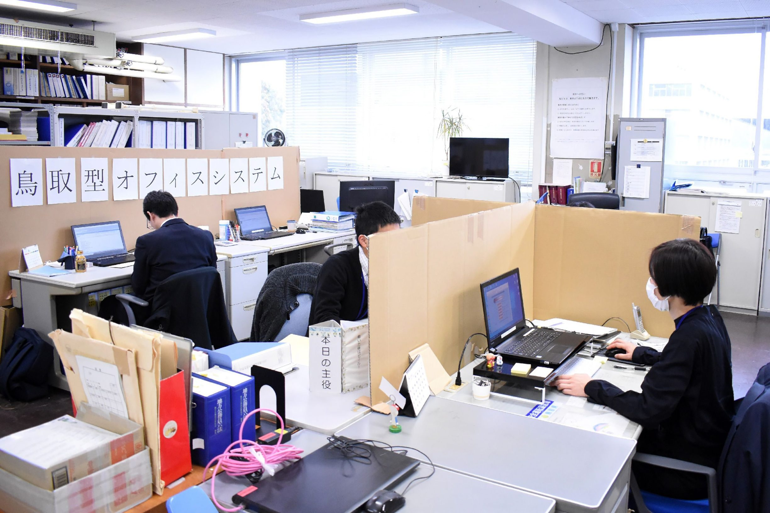 In this picture taken on April 1, 2020 office employees use cardboard partitions to separate their desks amid concerns over the COVID-19 coronavirus, at the prefectural government office in Tottori, western Japan. - As of April 1, Japan had registered 2,178 cases of the new coronavirus, with 57 deaths. (Photo by STR / JIJI PRESS / AFP) / Japan OUT