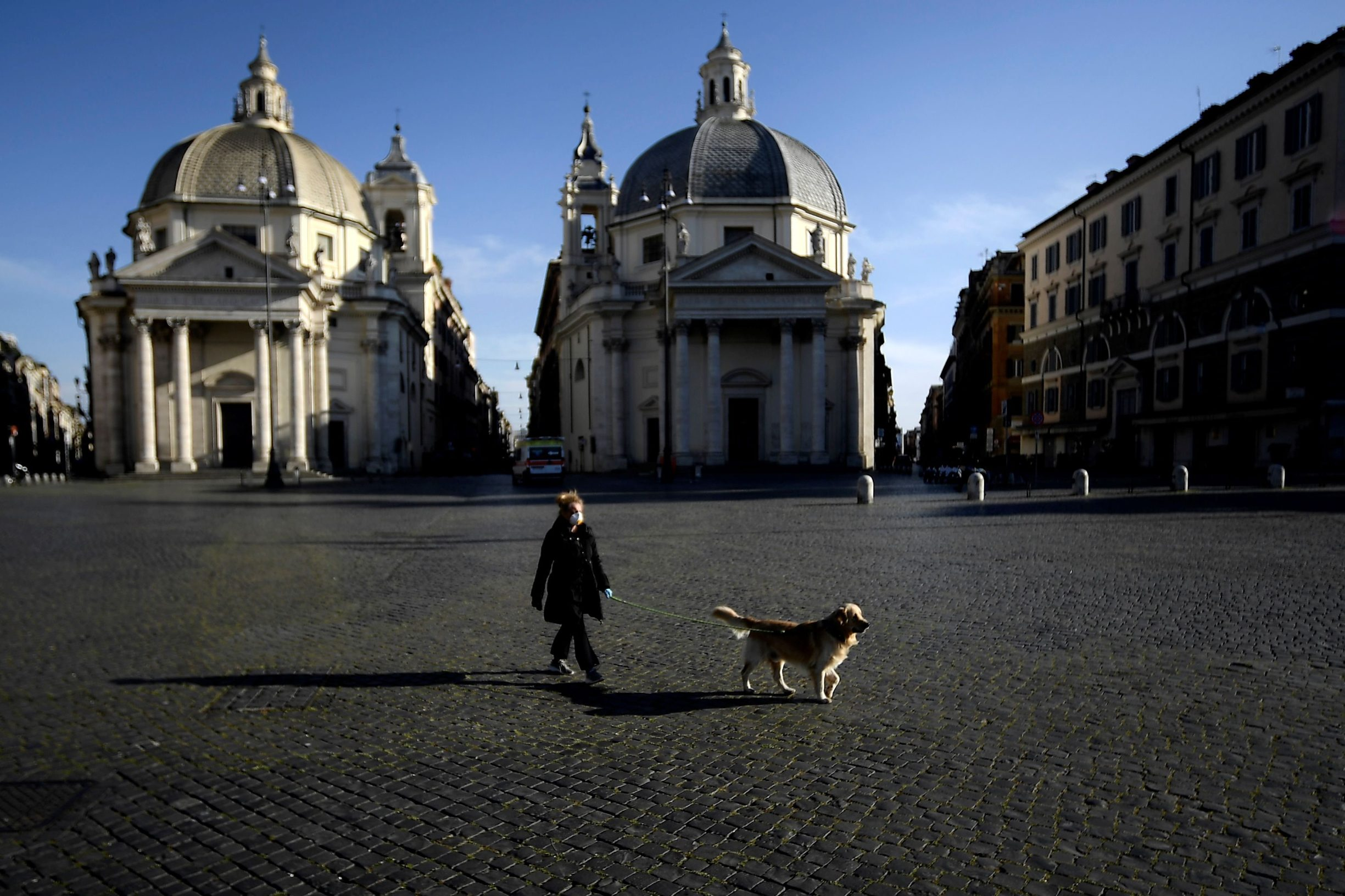 A woman takes her dog out in Piazza del Popolo on April 2, 2020 in Rome, during the country's lockdown aimed at curbing the spread of the COVID-19 infection, caused by the novel coronavirus. (Photo by Filippo MONTEFORTE / AFP)