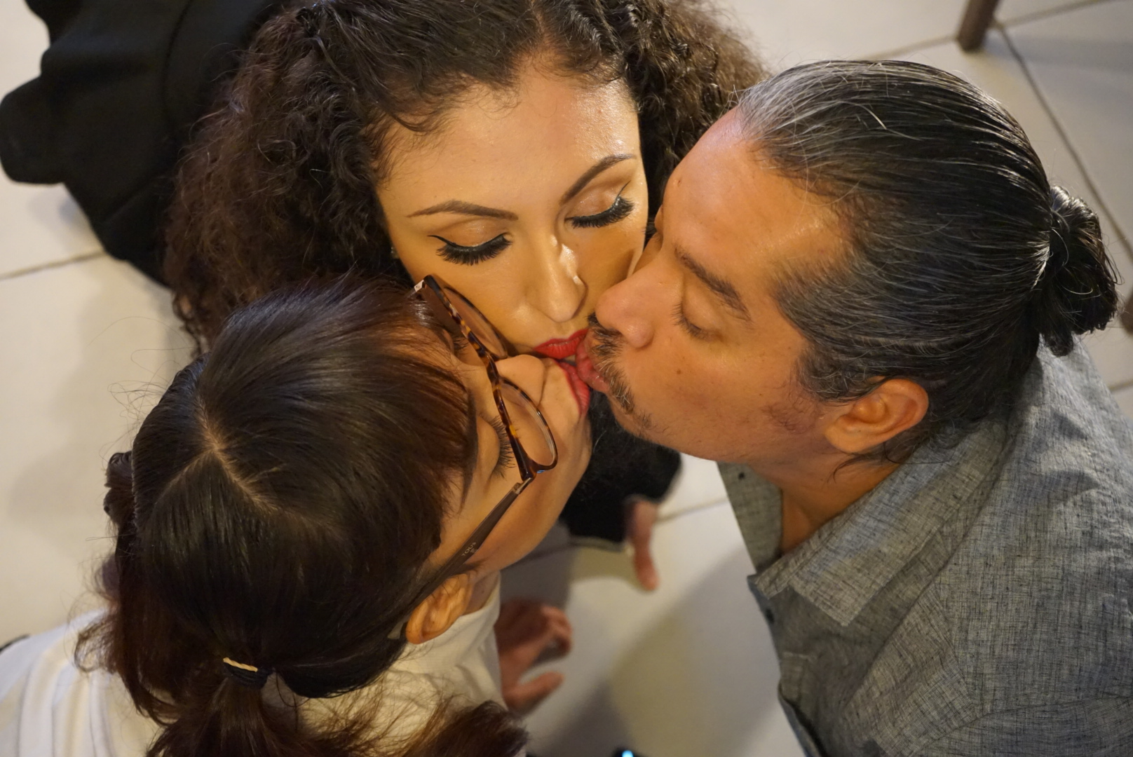 Lucy, Melin and Rodrigo kissing each other. MONTERREY CITY, MEXICO: THIS COUPLE married ONE WEEK AFTER THEY FIRST MET and have since invited a woman TWENTY-THREE YEARS his junior to join their relationship. On May 14, 2012, marketing entrepreneur, Rodrigo Contreras Diaz (41) from Monterrey City, Mexico, met his now wife, nutritionist, Melin Velasco Reyes (31) from Guadalajara City, through a mutual friend. Sparks flew instantly and Rodrigo ended up proposing to Melin that same day, to which she agreed. After just a week of preparations, they got married on May 21, 2012. Despite only having eyes for her, he explained to her early on in their relationship that he didn?t want a traditional monogamous relationship as he lived an alternative lifestyle and was open to a polyamorous relationship, which she accepted. For four years they focussed on their relationship then re-visited their exploration of other forms of partnerships and searched for another woman to join them in their union. On April 27, 2016, whilst they were both at a bar, they met one of the waitresses, Lucy (18), who was in high school at the time. Initially Lucy was shocked when Rodrigo began flirting with her in front of Melin, but after a few hours of chatting, they became closer and formed a polyamorous relationship. Since then, he admits that the addition of Lucy has positively improved his marriage with Melin and they now all plan to get married as a throuple, although Melin and Lucy, who are both straight, do not have a sexual relationship. mediadrumworld.com / @trikytriad, Image: 510886271, License: Rights-managed, Restrictions: , Model Release: no, Credit line: mediadrumworld.com / @trikytriad / Media Drum World / Profimedia