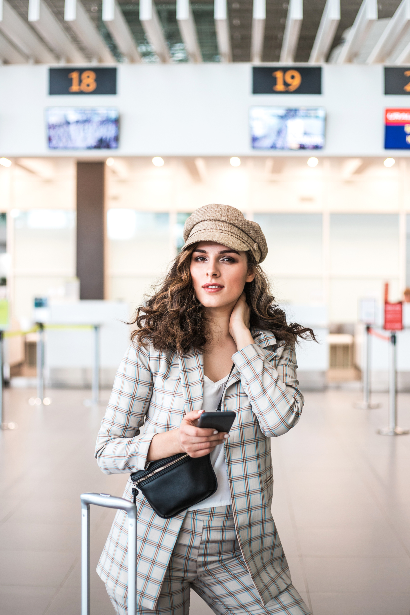 Young beautiful businesswoman reading phone messages in Airport waiting room.