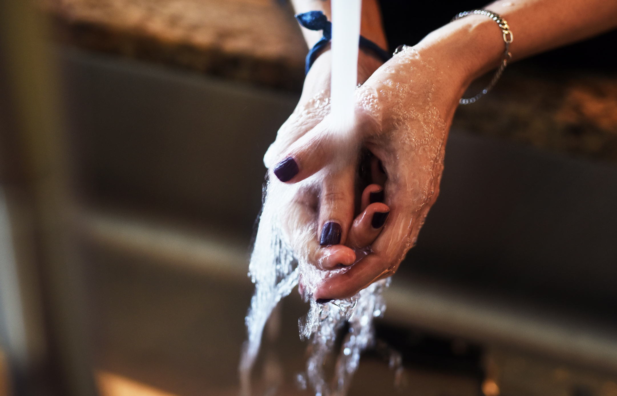 Closeup of an unrecognizable woman washing her hands under a tap at home during the day
