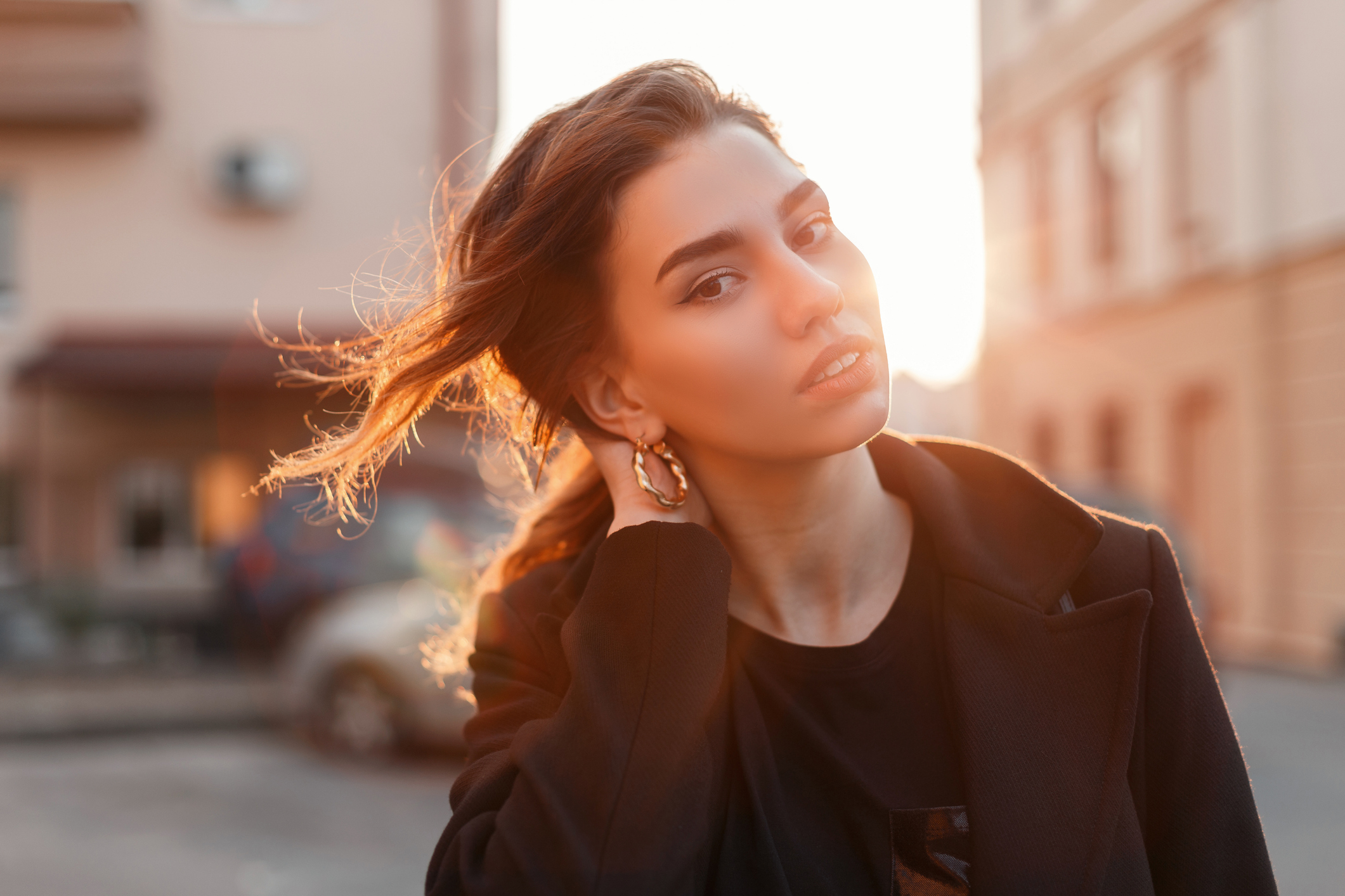 Portrait of a young cute attractive woman with a stylish hairstyle with beautiful eyes with sexy lips in fashionable black clothes on a background of bright orange spring sunset. Elegant girl relaxes.