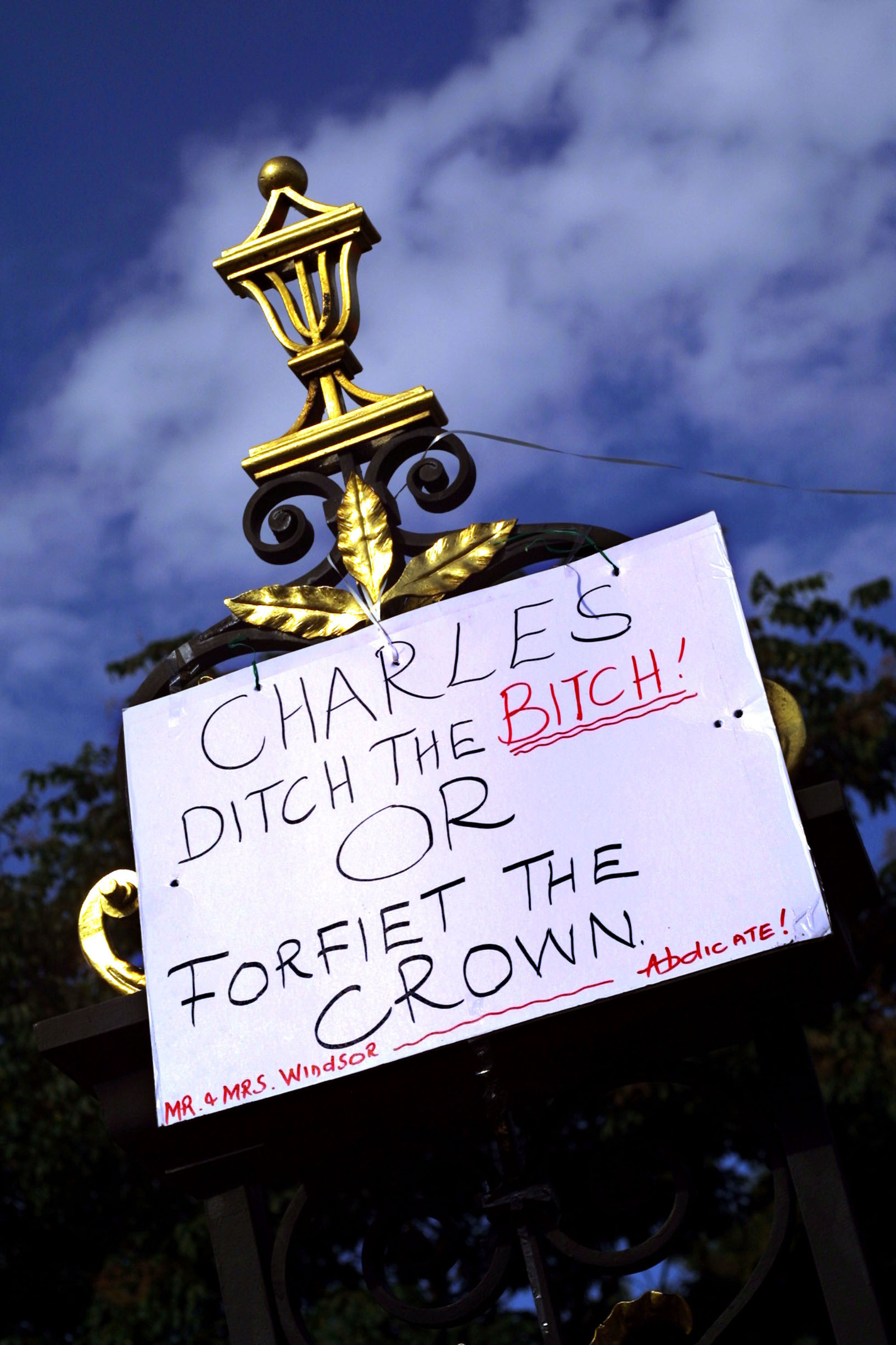 393903 07: A sign calling for Prince Charles to end his relationship with Camilla Parker-Bowles hangs at the gates of Kensington Palace on the 4th anniversary of the death of Diana, Princess of Wales, August 31, 2001 in London, United Kingdom. (Photo by Sion Touhig/Getty Images)