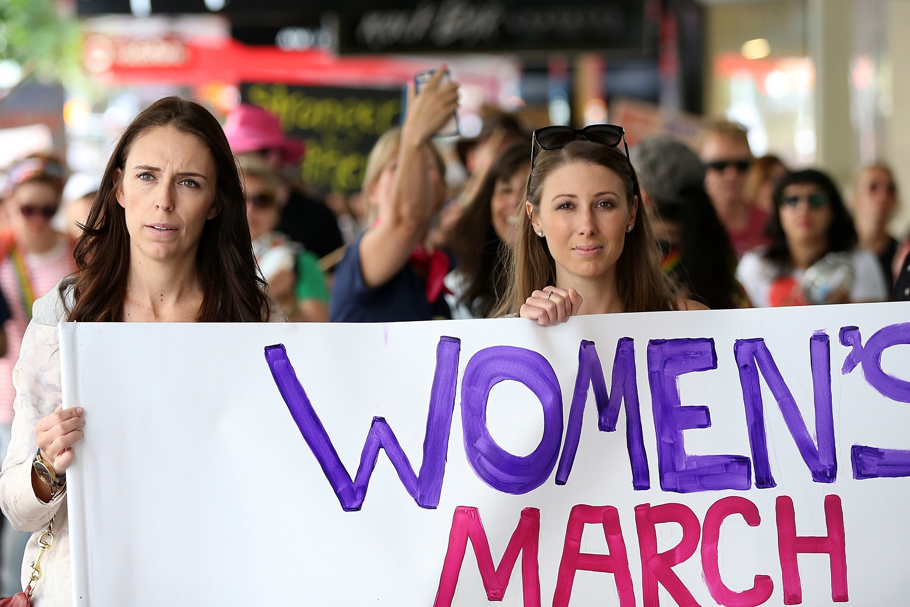 AUCKLAND, NEW ZEALAND - JANUARY 21:  Labour MP Jacinda Ardern (L) and musician, writer, activist Lizzie Marvelly (C) join thousands of people marching up Queen Street on January 21, 2017 in Auckland, New Zealand. The marches in New Zealand were organised to show solidarity with those marching on Washington DC and around the world in defense of women's rights and human rights.  (Photo by Fiona Goodall/Getty Images)