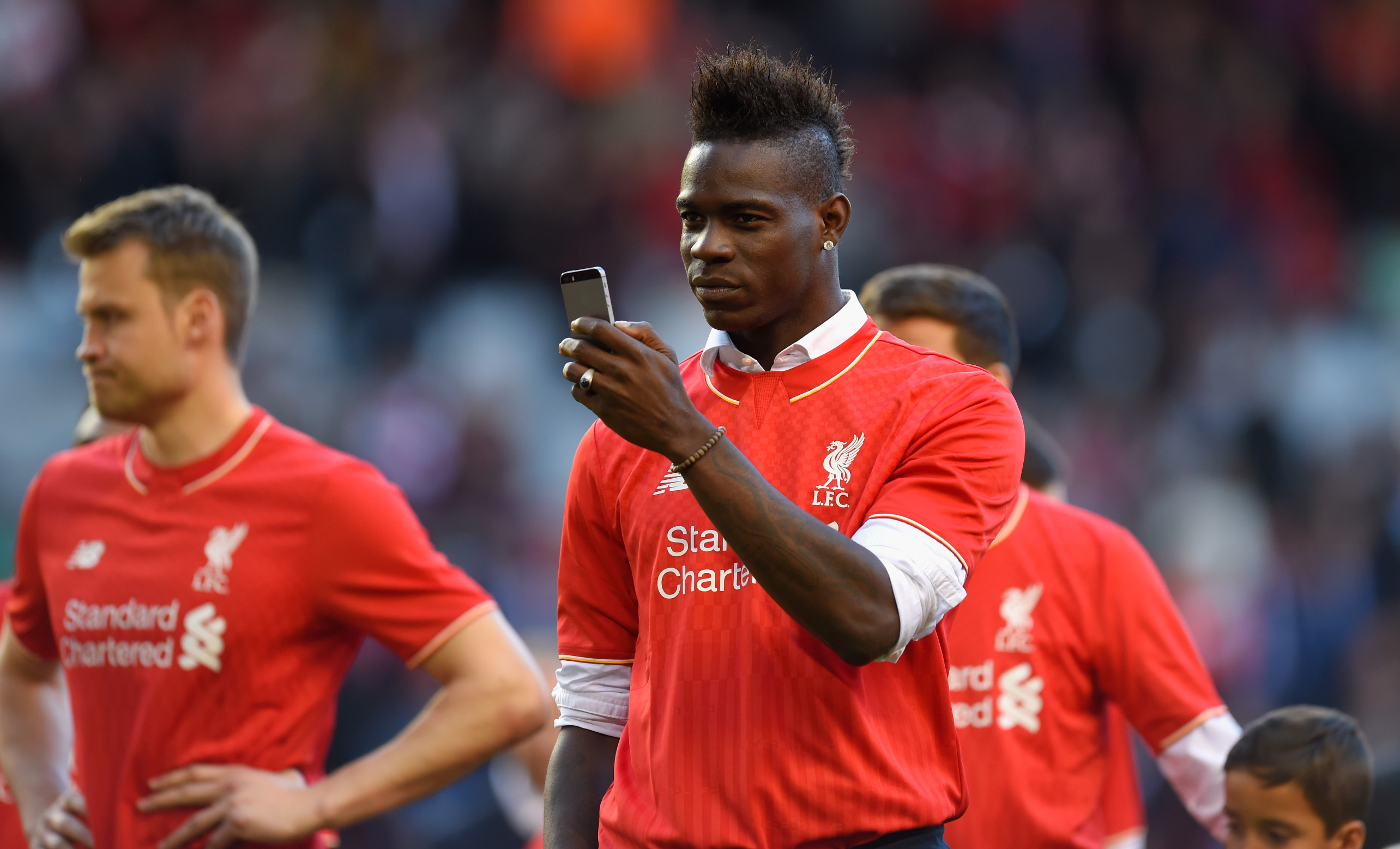 LIVERPOOL, ENGLAND - MAY 16:  Mario Balotelli of Liverpool takes pictures of the fans on his phone after the Barclays Premier League match betrween Liverpool and Crystal Palace at Anfield on May 16, 2015 in Liverpool, England.  (Photo by Stu Forster/Getty Images)