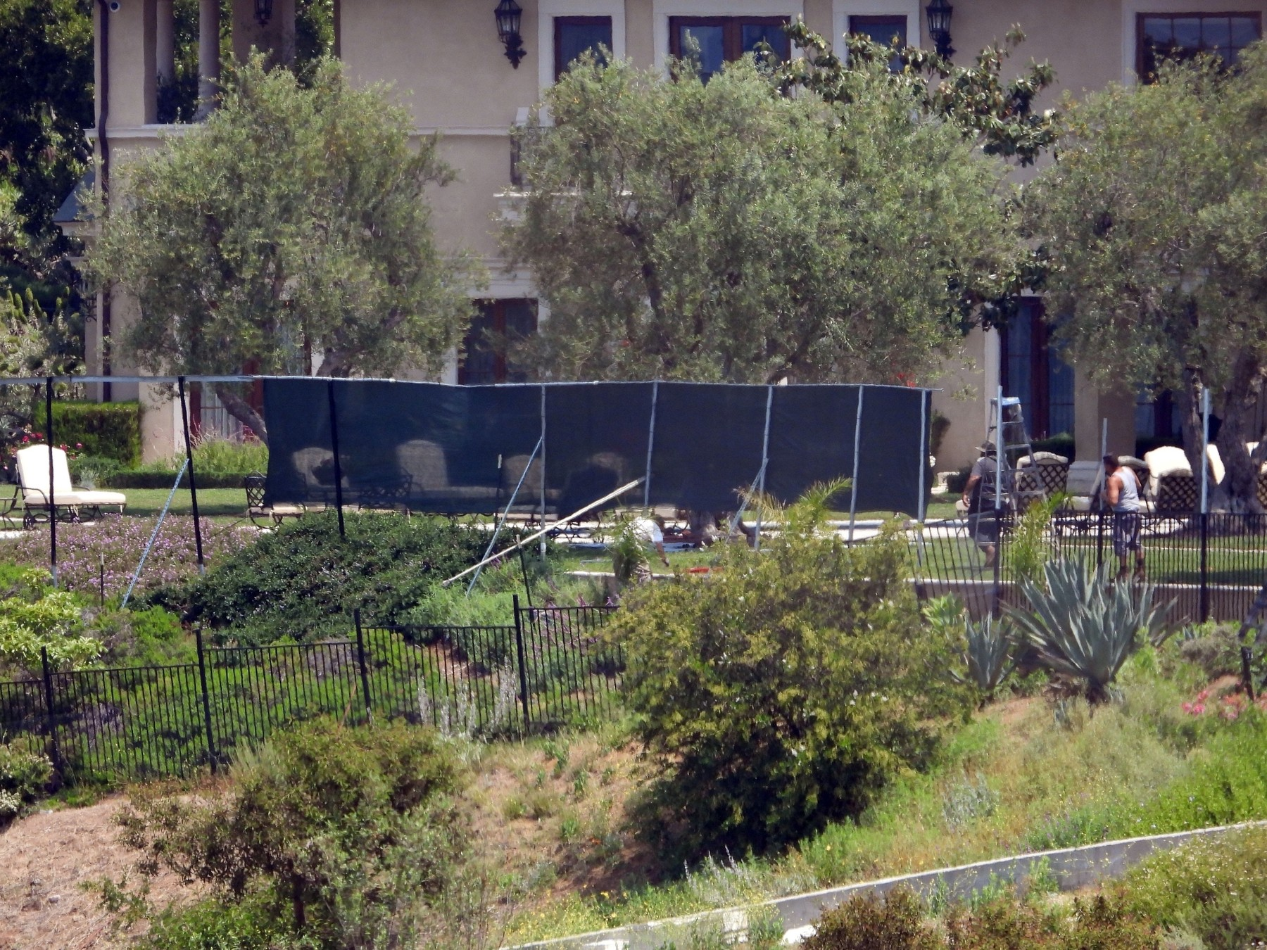 Beverly Hills, CA  - *EXCLUSIVE*  - New screens are erected by workmen at the Beverly Hills mansion owned by Tyler Perry, now reportedly the American home of Prince Harry, his wife Meghan Markle and their baby son, Archie. These photos were taken from a hiking trail close to the  million property which opened to the public on Saturday, May 9, 2020. A hiking trail leads up a steep hill to the edge of the property, where a security camera is situated. There are also security cameras set up on fences dotted around the home. From the mansion, it is also possible for the Duke and Duchess of Sussex to look down at the homes of showbiz royalty Sylvester Stallone, Mark Wahlberg and Rod Stewart who all own multi-million dollar mansions in the neighboring Beverly Park estate. Sylvester Stallone's home is the one with the outdoor pool, Rod Stewart's is the French-style mansion and it is just possible to see his soccer pitch, while Mark Wahlberg's home has what appears to be a circular turret.  BACKGRID USA 11 MAY 2020, Image: 518624906, License: Rights-managed, Restrictions: , Model Release: no, Credit line: BACKGRID / Backgrid USA / Profimedia