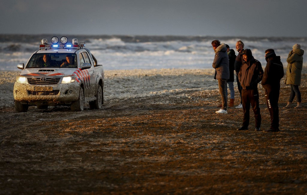 People look at a police car on a beach after a group of surfers was reported in trouble at the Noordelijk Havenhoofd, near the coastal town of Scheveningen, The Netherlands on May 11, 2020. - Emergency services found three of them, and brought them out of the water, two of whom later died. (Photo by Sem VAN DER WAL / ANP / AFP) / Netherlands OUT
