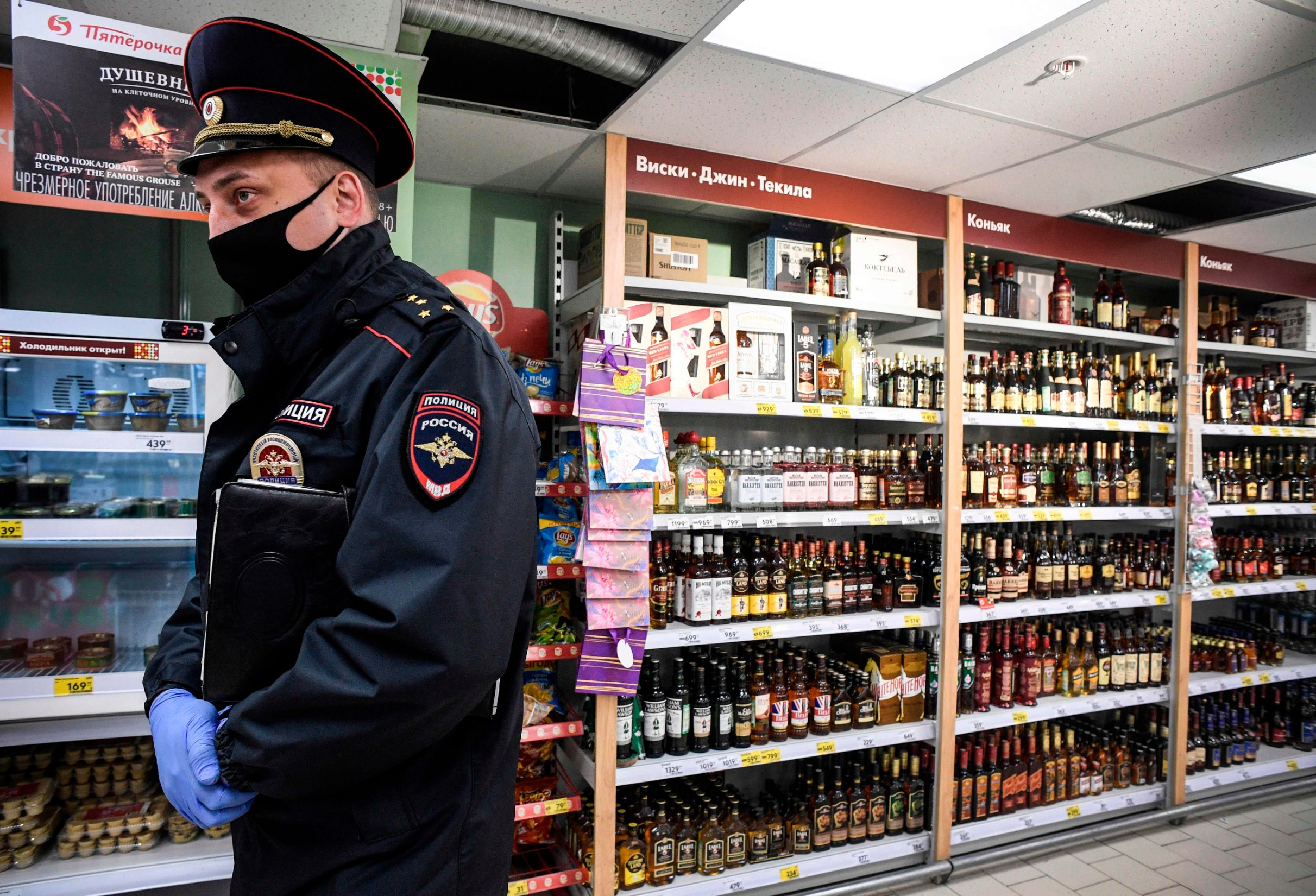 A Russian police officer wearing a protective mask patrol inside a supermarket in Moscow on May 13, 2020, amid the spread of the COVID-19 coronavirus. - To avoid the escalation of the number of infections, the city authorities have made it mandatory to wear gloves and a masks on public transport, shops and other pubic places, on pain of a fine of 5,000 rubles (about 63 euros). (Photo by Alexander NEMENOV / AFP)