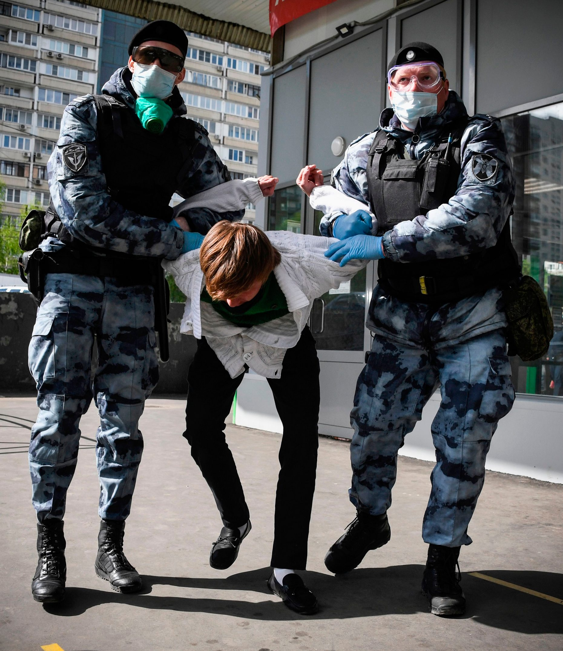 Russian serviceman of the Russian National Guard (Rosgvardia) detains a man in front of a supermarket in Moscow on May 13, 2020, amid the spread of the COVID-19 coronavirus. - To avoid an escalation in the number of infections, the city authorities have made it mandatory to wear gloves and a mask on public transport, shops and other pubic places, on pain of a fine of 5,000 rubles (about 63 euros). (Photo by Alexander NEMENOV / AFP)