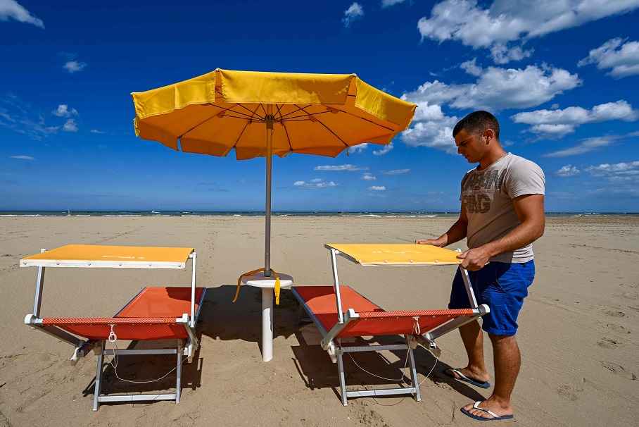 TOPSHOT - A view taken on May 11, 2020 on the seafront of Cesenatico on the Adriatic coast, northeastern Italy, shows beach manager Ramon Diego Gargiulo showing the positioning of sunbeds and sunshade as part of safety precautions for customers against the spread of COVID-19 during the upcoming summer season, during the country's lockdown aimed at curbing the spread of the COVID-19 infection, caused by the novel coronavirus. - With the tourism sector reeling, the European Commission was on May 13, 2020 to present a rescue plan for the sector. (Photo by Vincenzo PINTO / AFP)